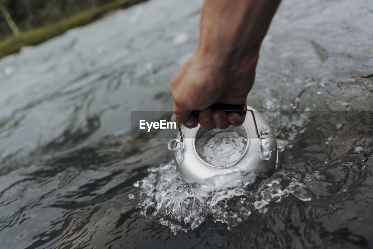 Cropped hand filling water in tea kettle