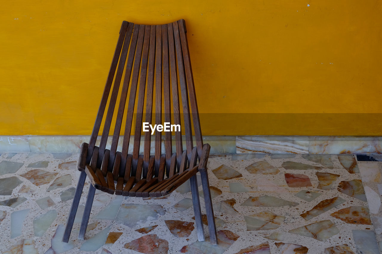 Close-up of empty chair against yellow wall