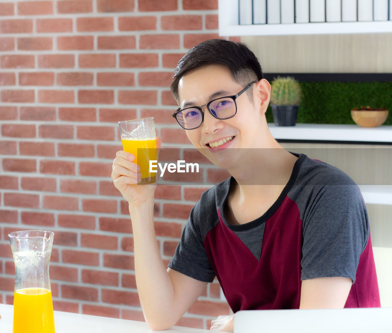 PORTRAIT OF A SMILING YOUNG MAN DRINKING GLASSES