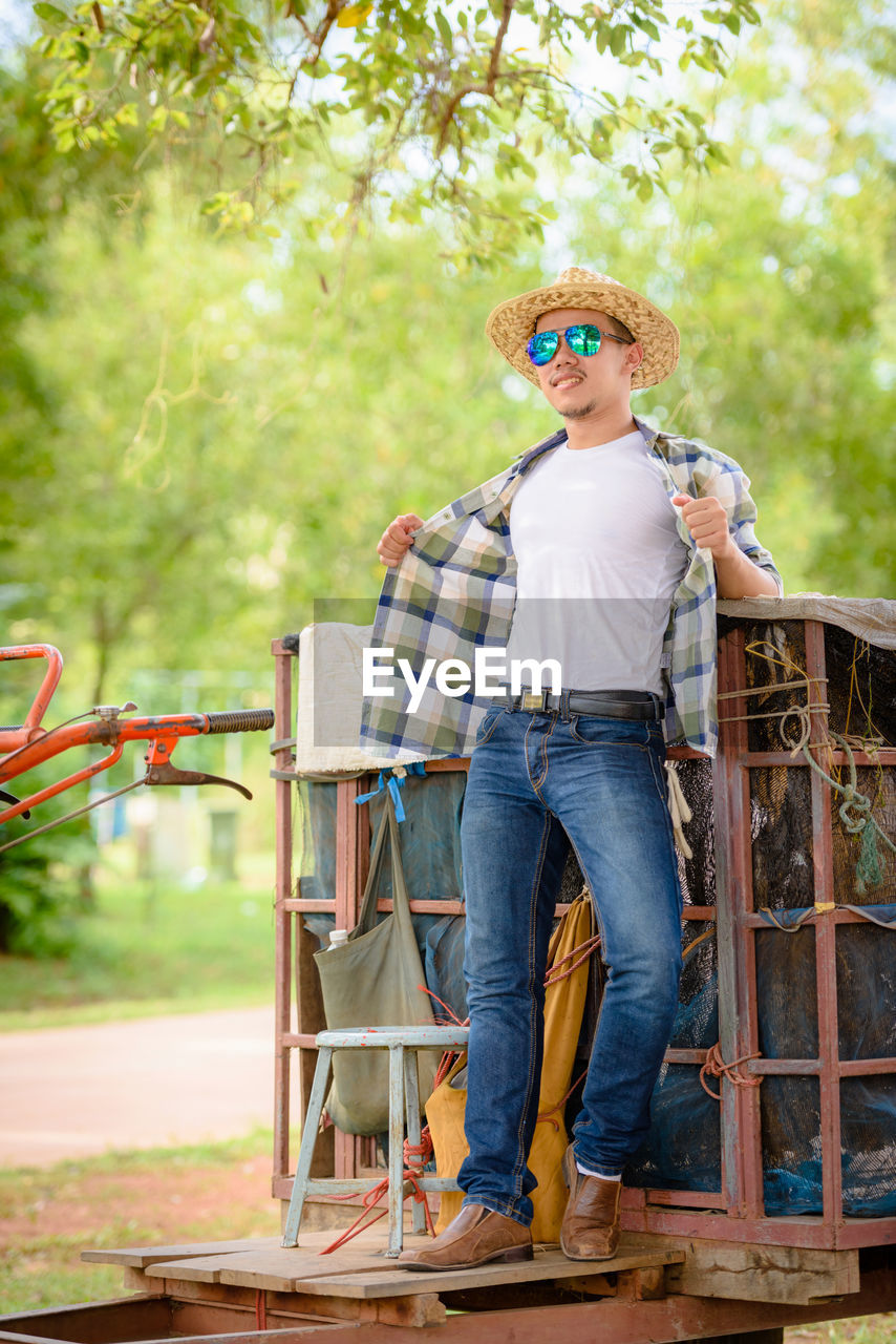 Full length of farmer standing on tractor at field