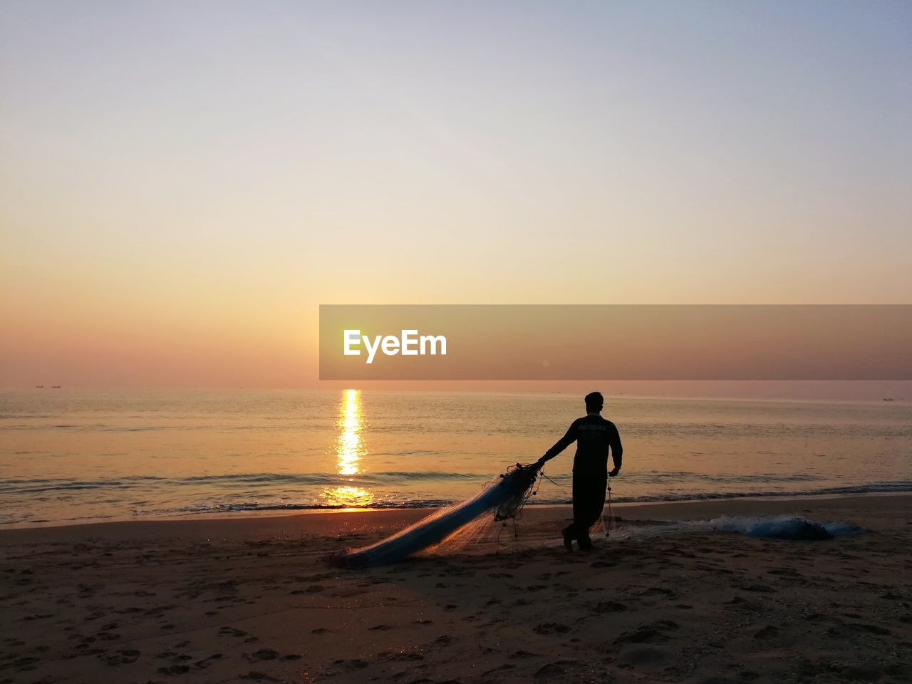 sunset, beach, sea, nature, water, real people, sand, beauty in nature, shore, horizon over water, scenics, sky, full length, sun, silhouette, outdoors, lifestyles, one person, standing, clear sky, men, wave, day, people