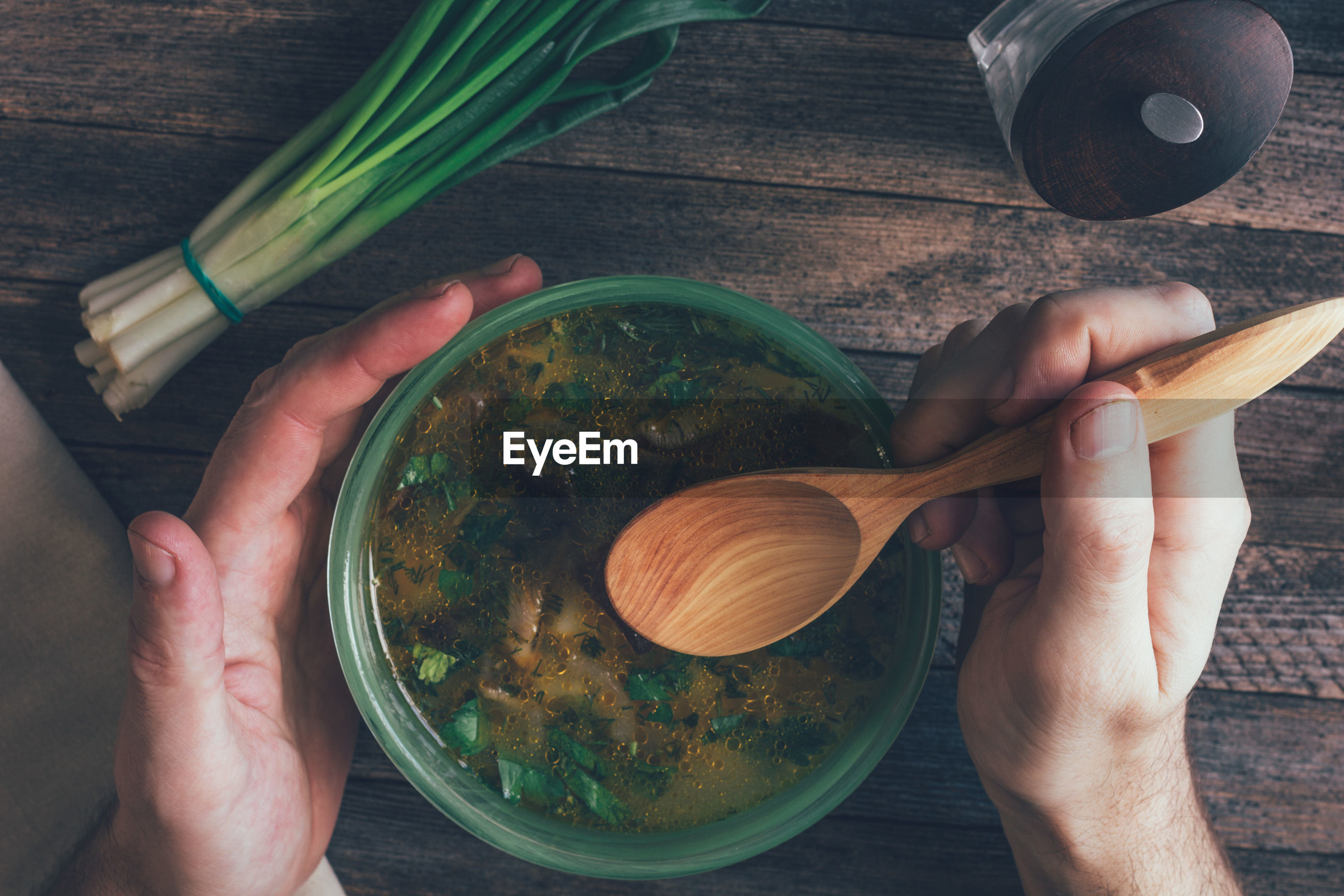 Man eats mushroom soup, green onions, pepper mill and a wooden spoon on old wooden table