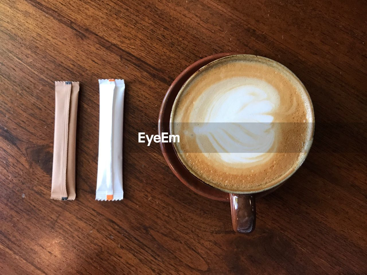 table, coffee - drink, coffee cup, food and drink, refreshment, frothy drink, drink, still life, froth art, cappuccino, indoors, directly above, high angle view, wood - material, no people, freshness, latte, close-up, day
