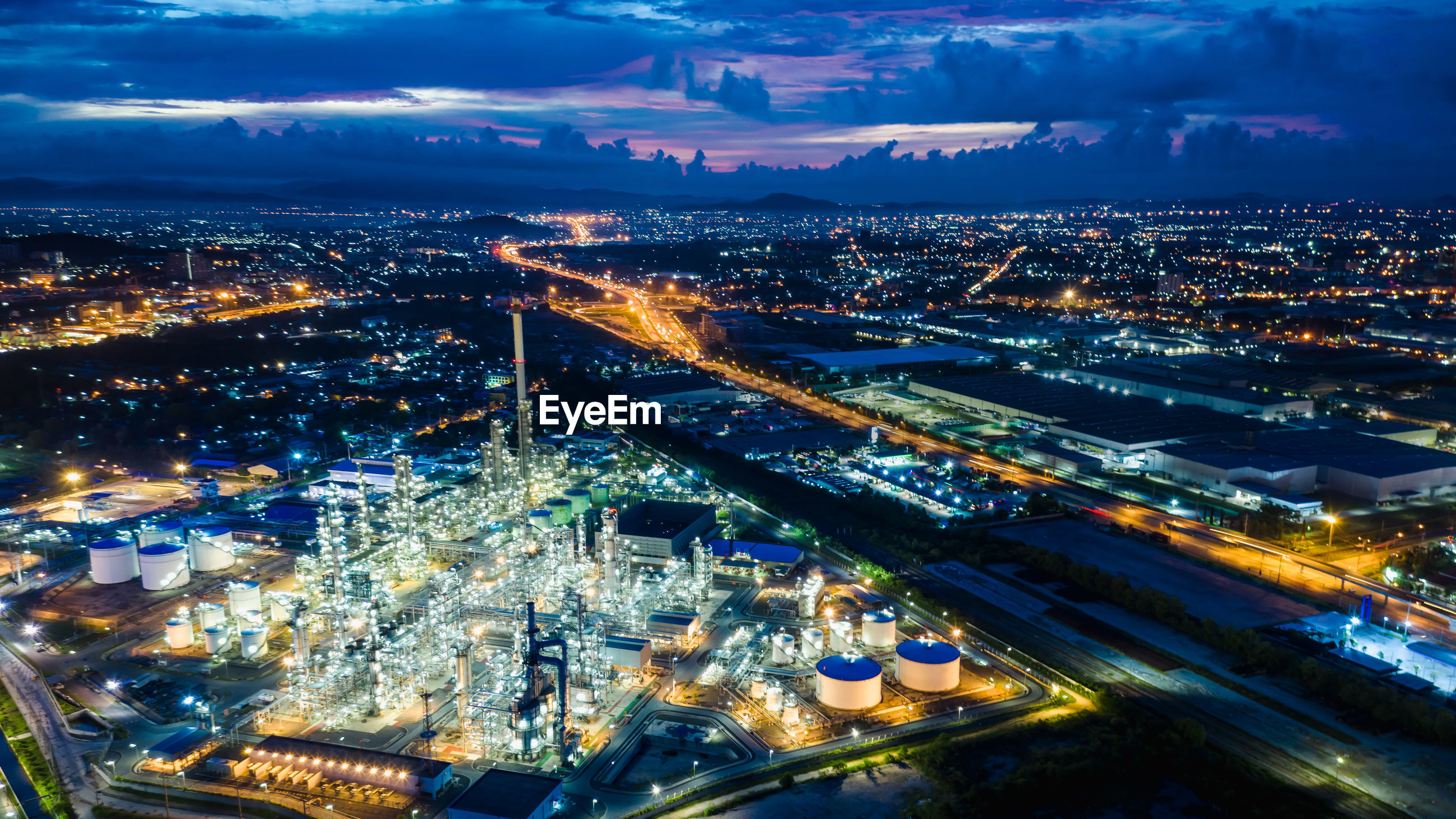 High angle view refinery of illuminated city buildings at night