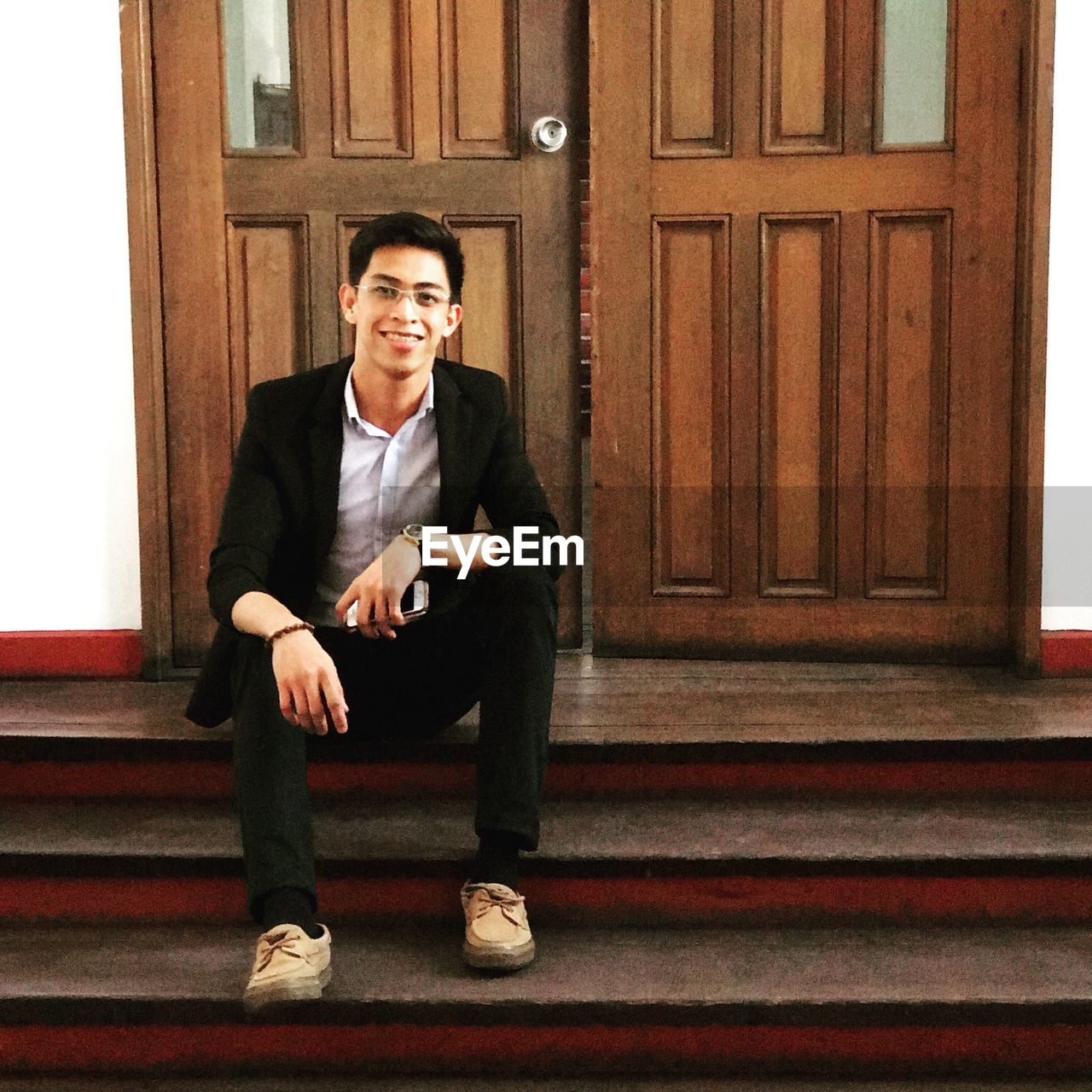 Portrait of young man sitting on steps against door
