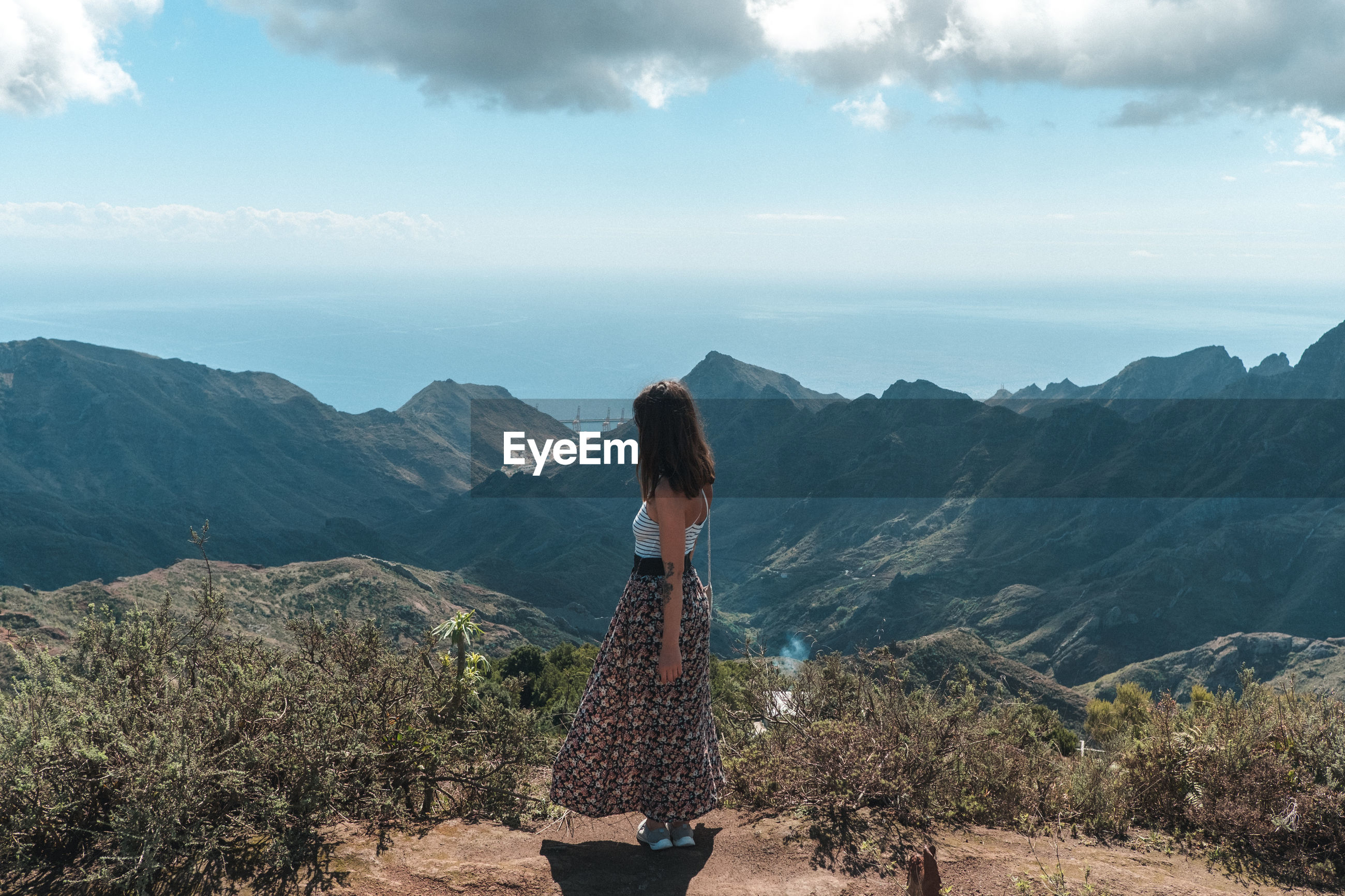 Woman looking at mountains against sky