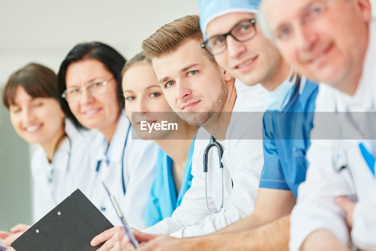 occupation, group of people, adult, healthcare and medicine, doctor, men, clothing, stethoscope, indoors, lab coat, young adult, hospital, women, professional occupation, cooperation, medical instrument, young men, teamwork, real people, healthcare worker, coworker, care