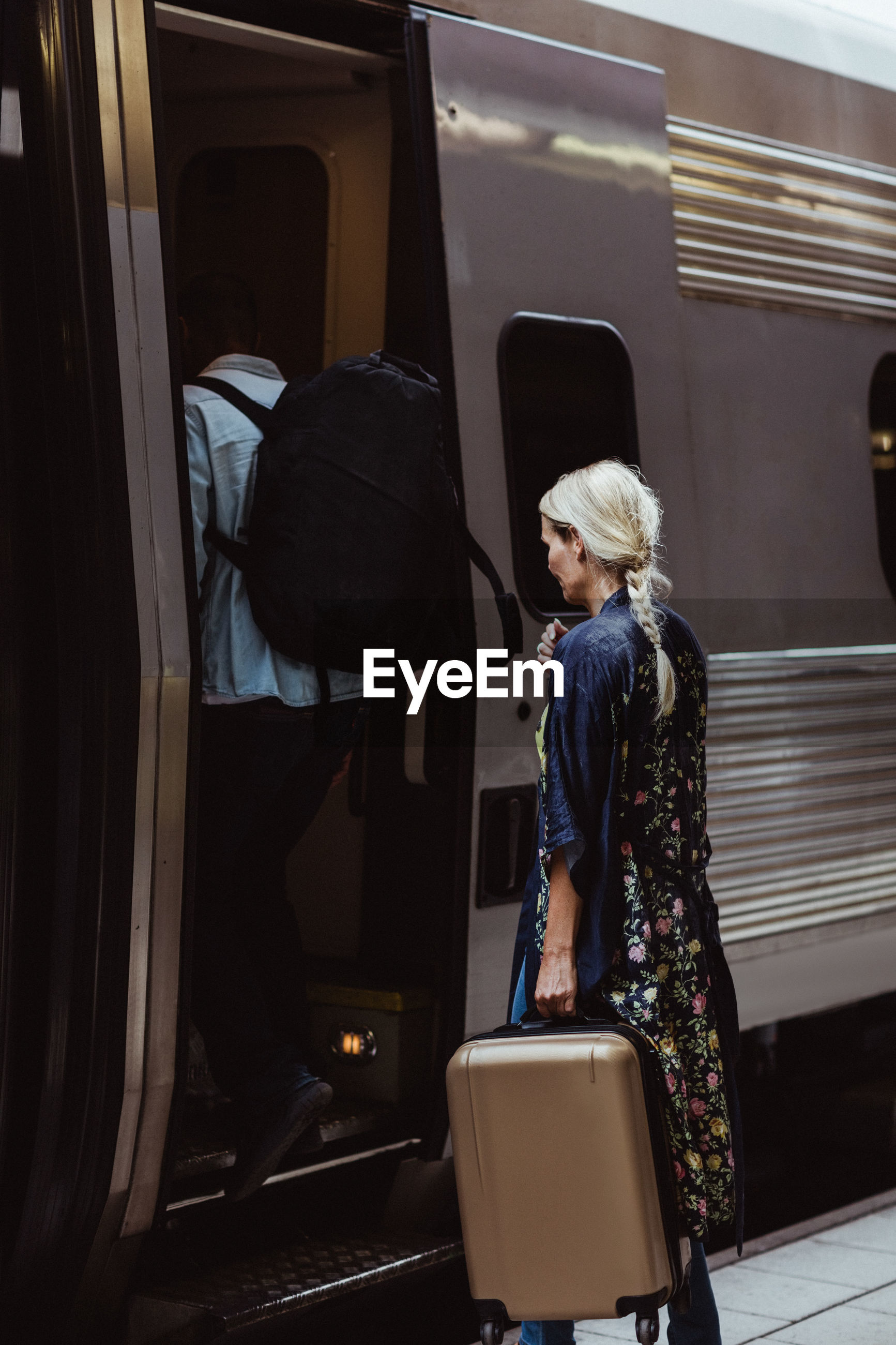REAR VIEW OF WOMAN STANDING BY TRAIN AT BUS