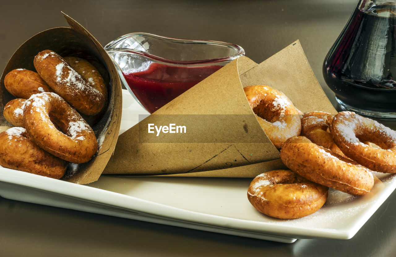 Close-Up Of Donuts With Powdered Sugar And Rolled Cardboard In Plate On Table