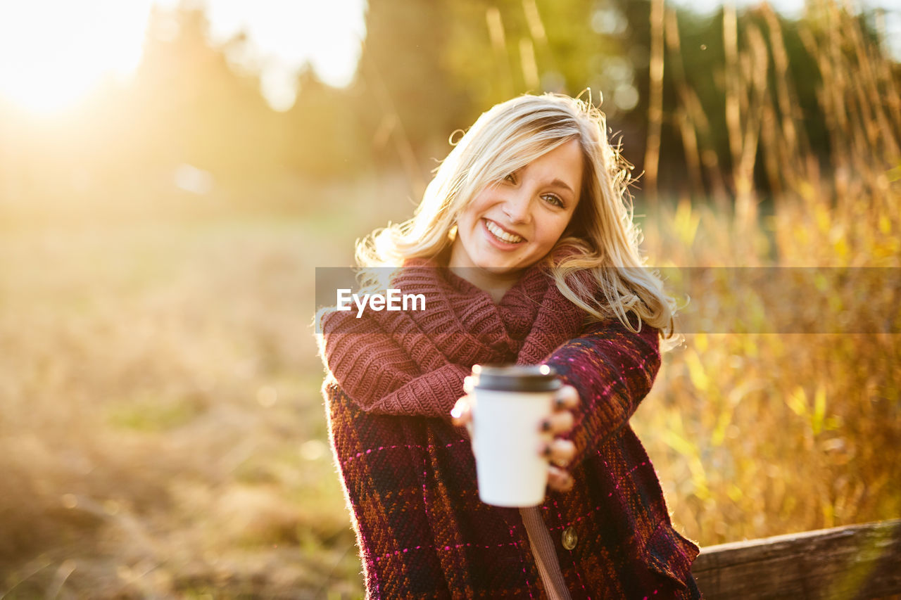 Young Woman Holding Coffee Cup While Standing On Field