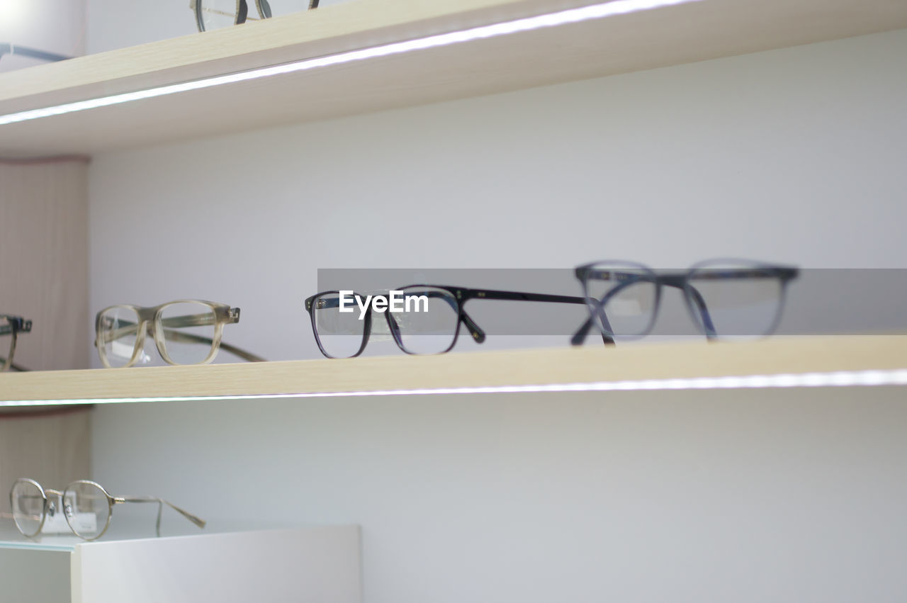 indoors, no people, shelf, white color, glasses, close-up, eyeglasses, wall - building feature, home interior, domestic room, still life, home, coathanger, hanging, absence, metal, communication, rack, furniture, focus on foreground, personal accessory