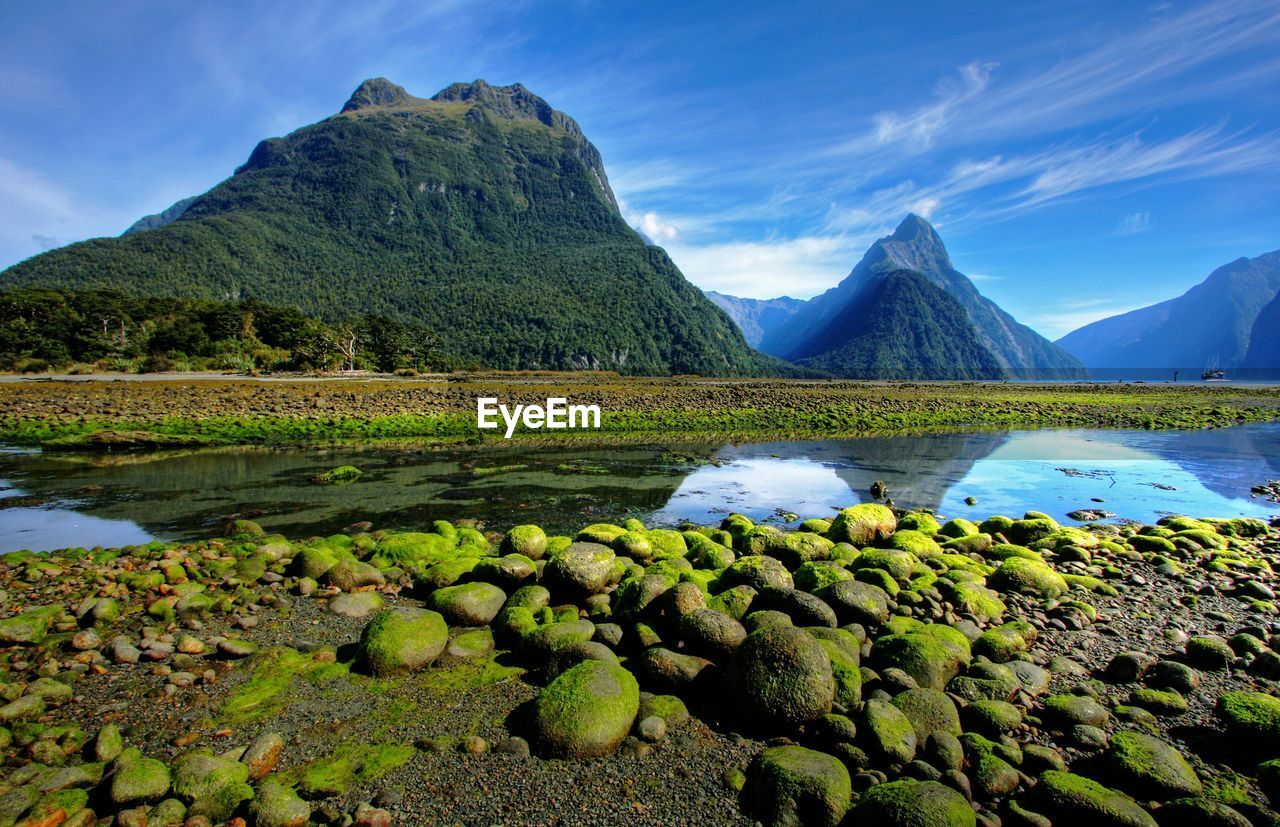 mountain, water, scenics - nature, beauty in nature, tranquil scene, tranquility, sky, lake, nature, rock, no people, mountain range, cloud - sky, non-urban scene, solid, green color, idyllic, plant, day, outdoors, mountain peak