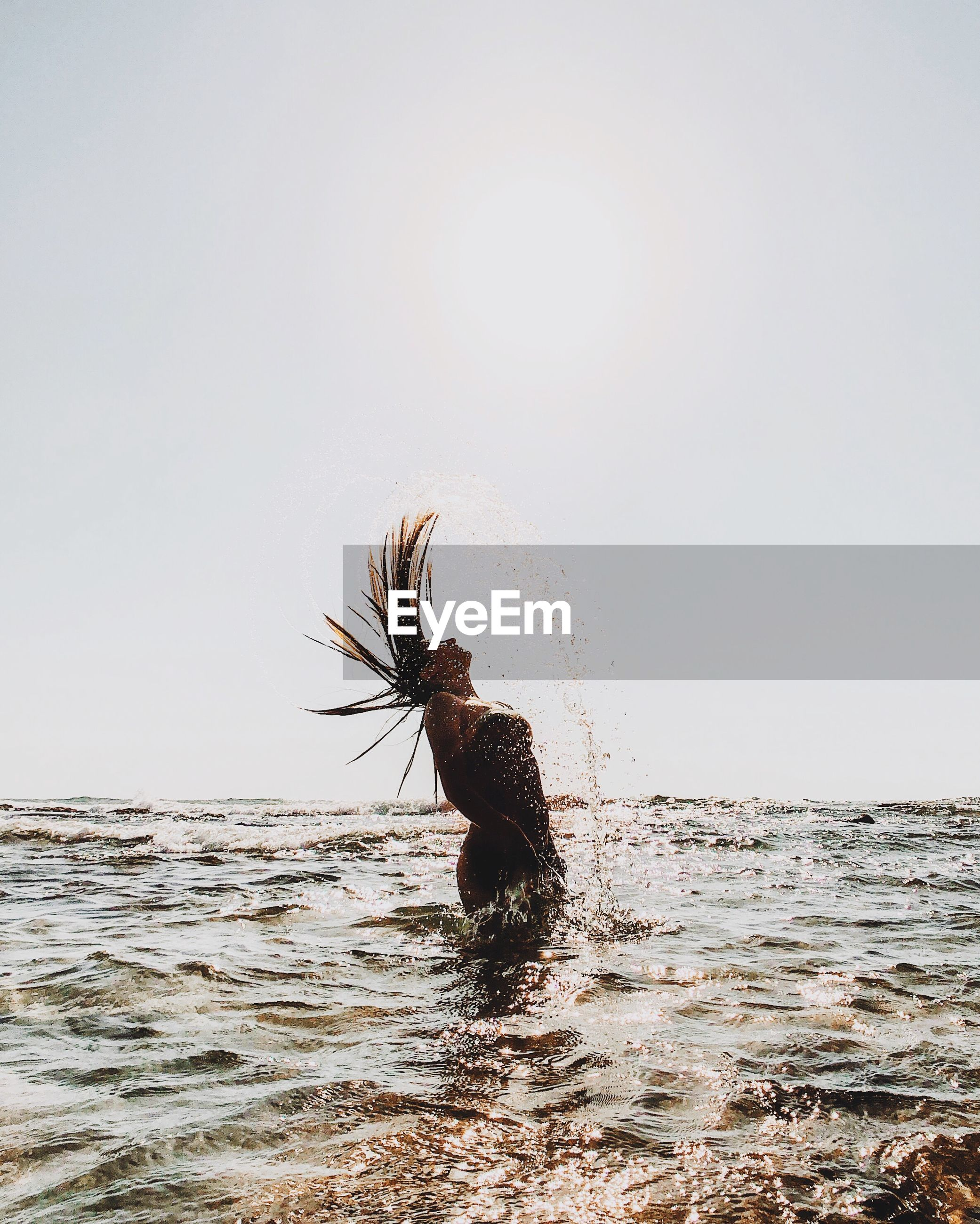 Side view of teenage girl tossing hair while standing in sea against clear sky