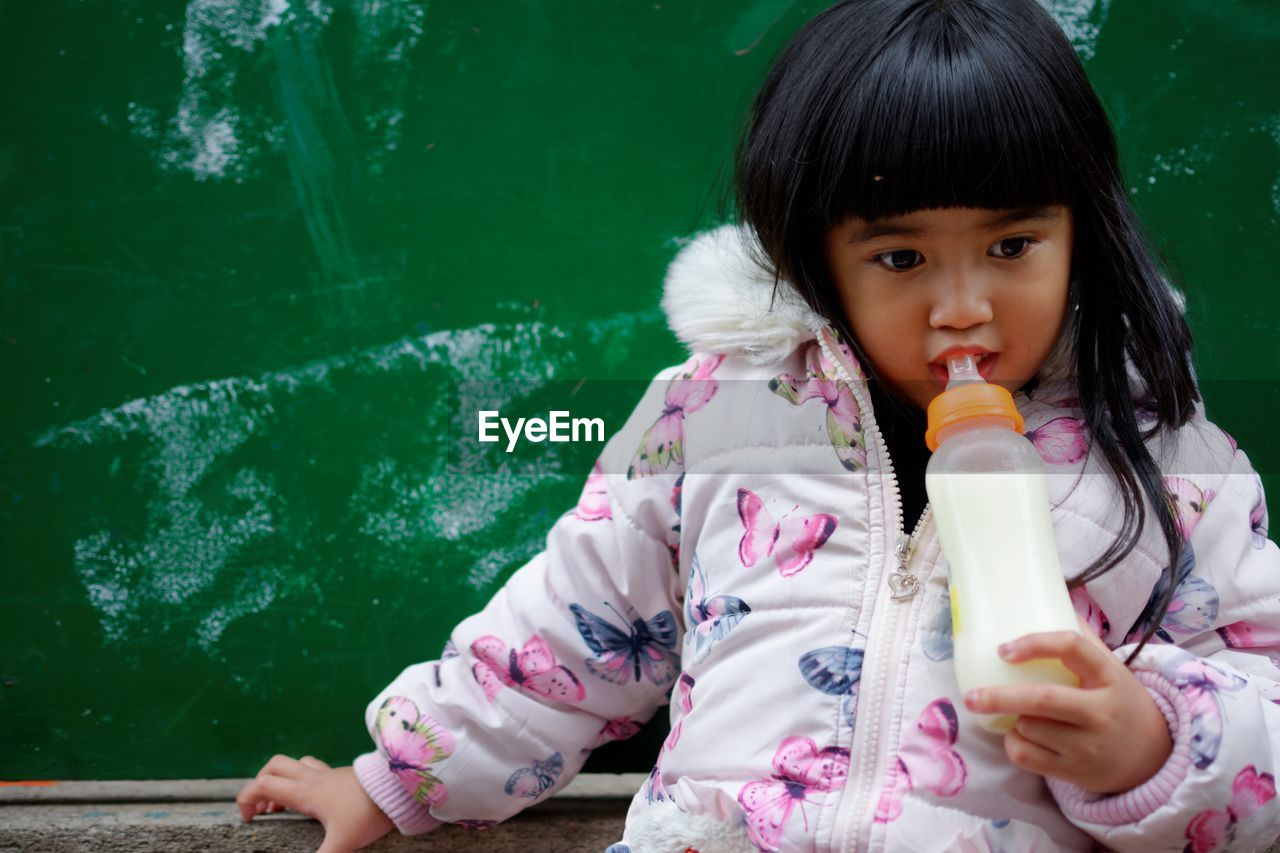 Cute Girl Drinking Milk From Bottle Against Wall