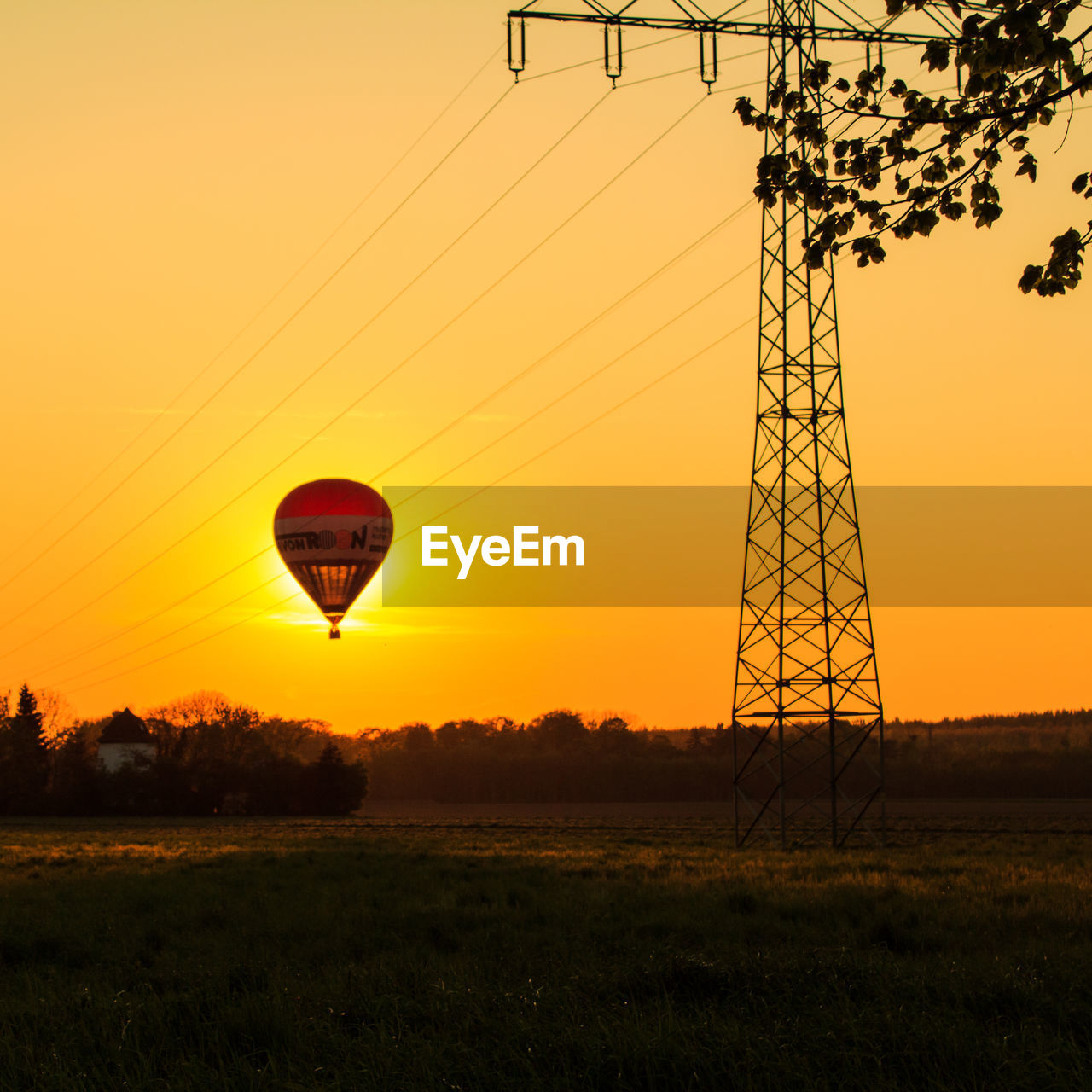 sky, sunset, hot air balloon, nature, field, land, air vehicle, environment, balloon, transportation, landscape, electricity pylon, orange color, no people, plant, technology, beauty in nature, mid-air, electricity, flying, outdoors, power supply