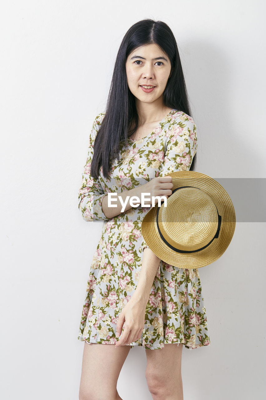 one person, standing, three quarter length, looking at camera, portrait, hat, front view, young women, studio shot, hair, indoors, clothing, holding, young adult, long hair, casual clothing, white background, hairstyle, women, lifestyles, fashion, beautiful woman, floral pattern