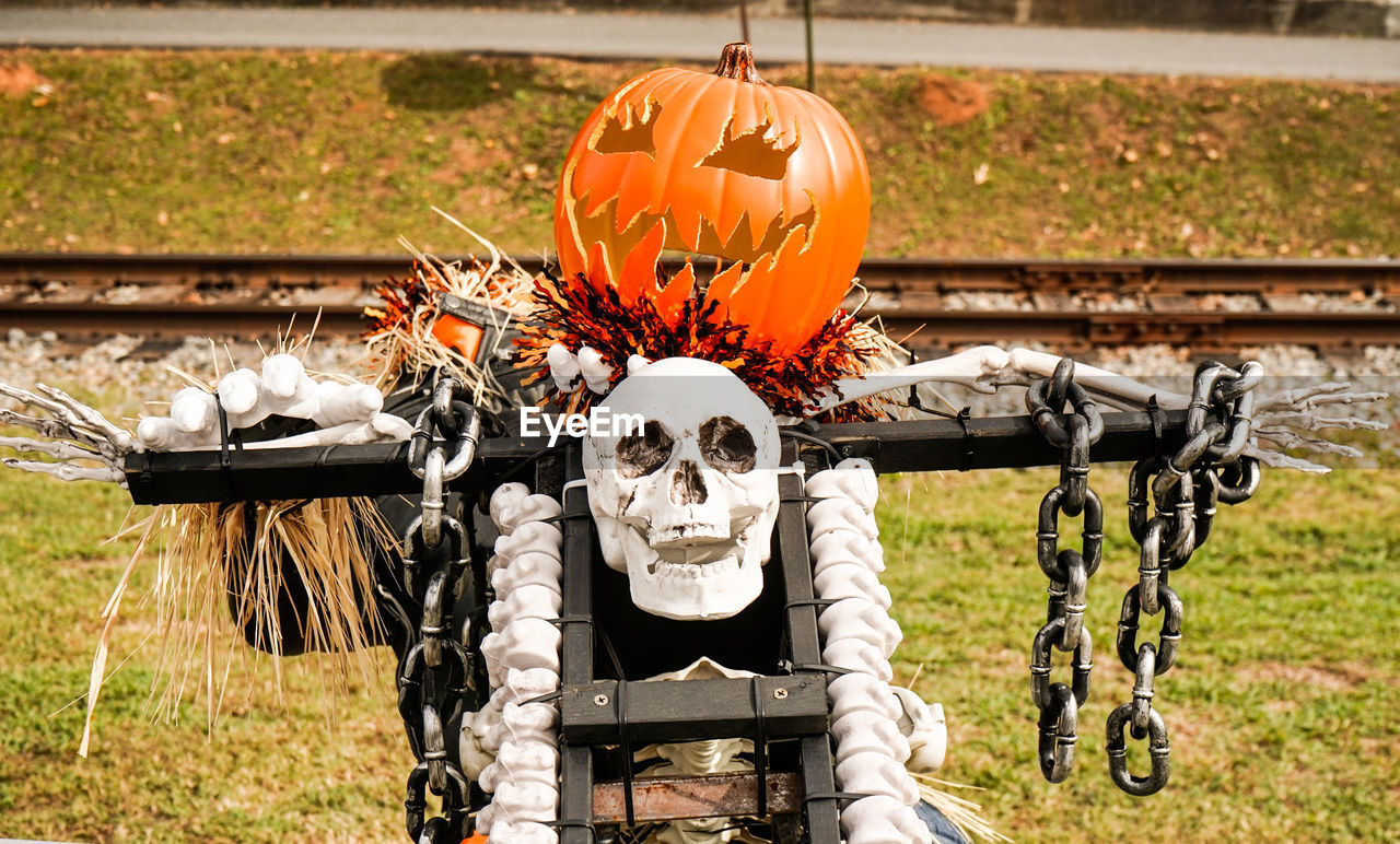 representation, no people, day, halloween, creativity, focus on foreground, human representation, celebration, pumpkin, art and craft, nature, orange color, anthropomorphic, outdoors, face, anthropomorphic face, field, mode of transportation, food, male likeness