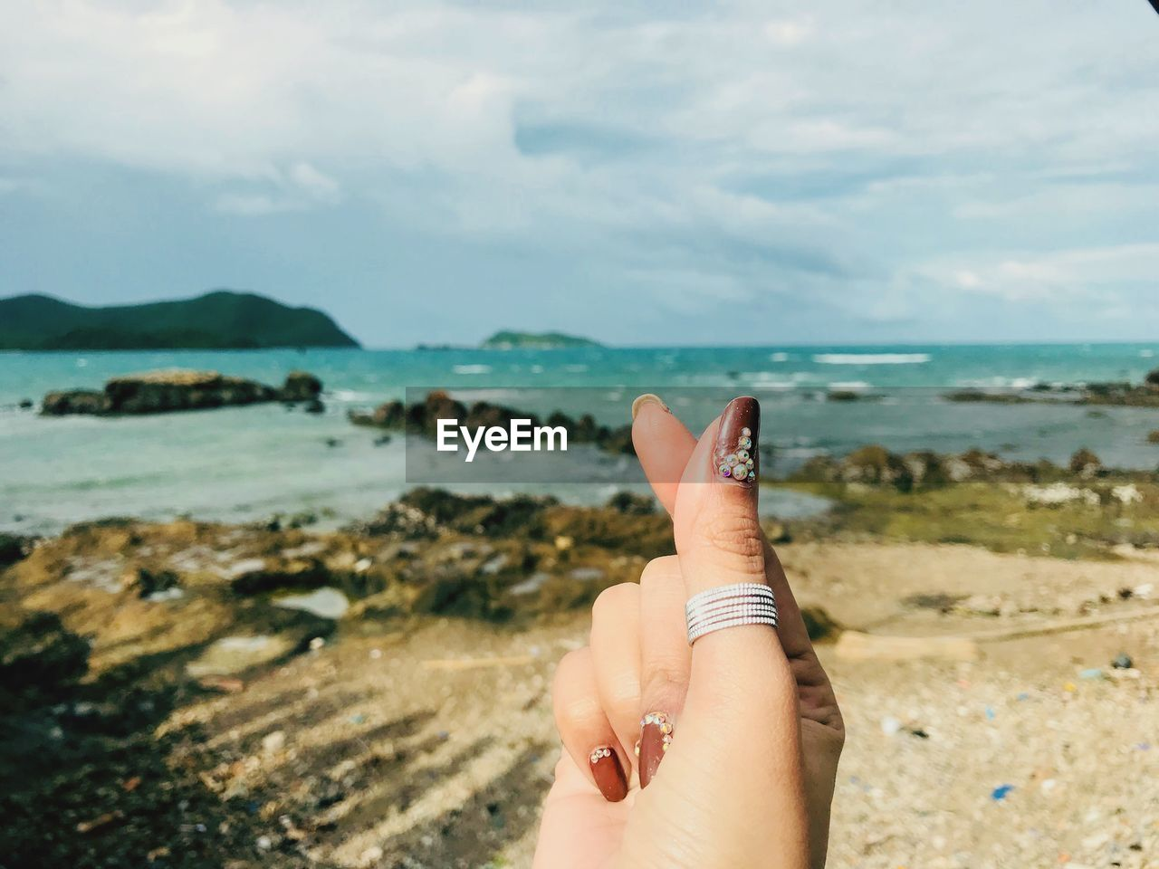 human body part, one person, human hand, sky, sea, water, hand, real people, beach, body part, land, nature, human finger, personal perspective, lifestyles, finger, day, focus on foreground, outdoors, horizon over water, nail