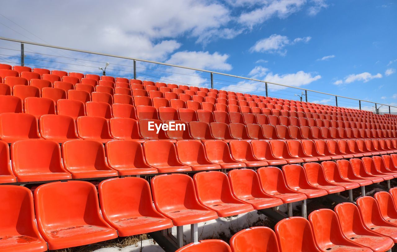 seat, empty, red, chair, in a row, stadium, absence, sport, no people, orange color, side by side, sky, repetition, arrangement, bleachers, day, soccer, nature, order, cloud - sky, outdoors