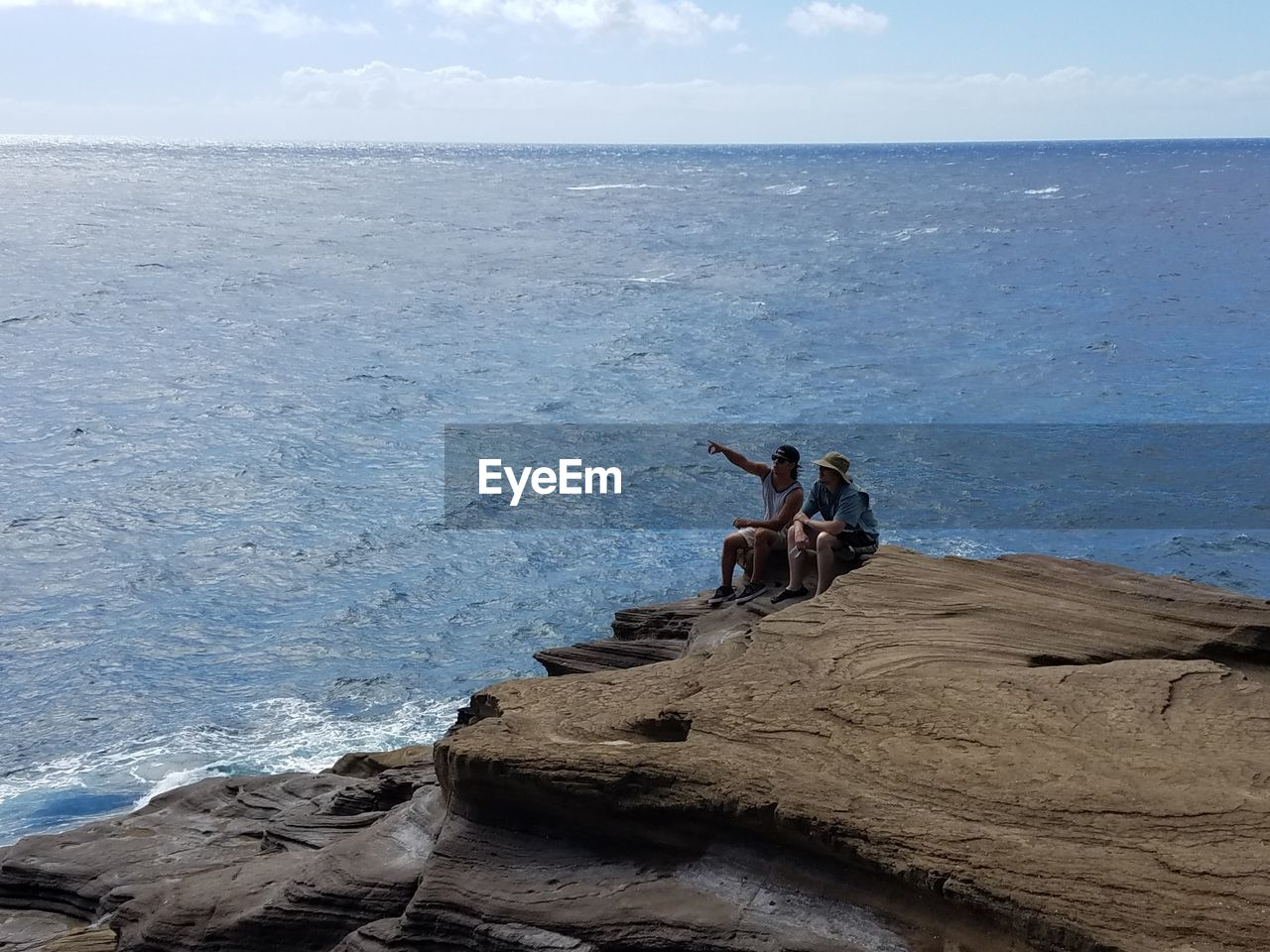 High angle view of friends sitting on cliff by sea