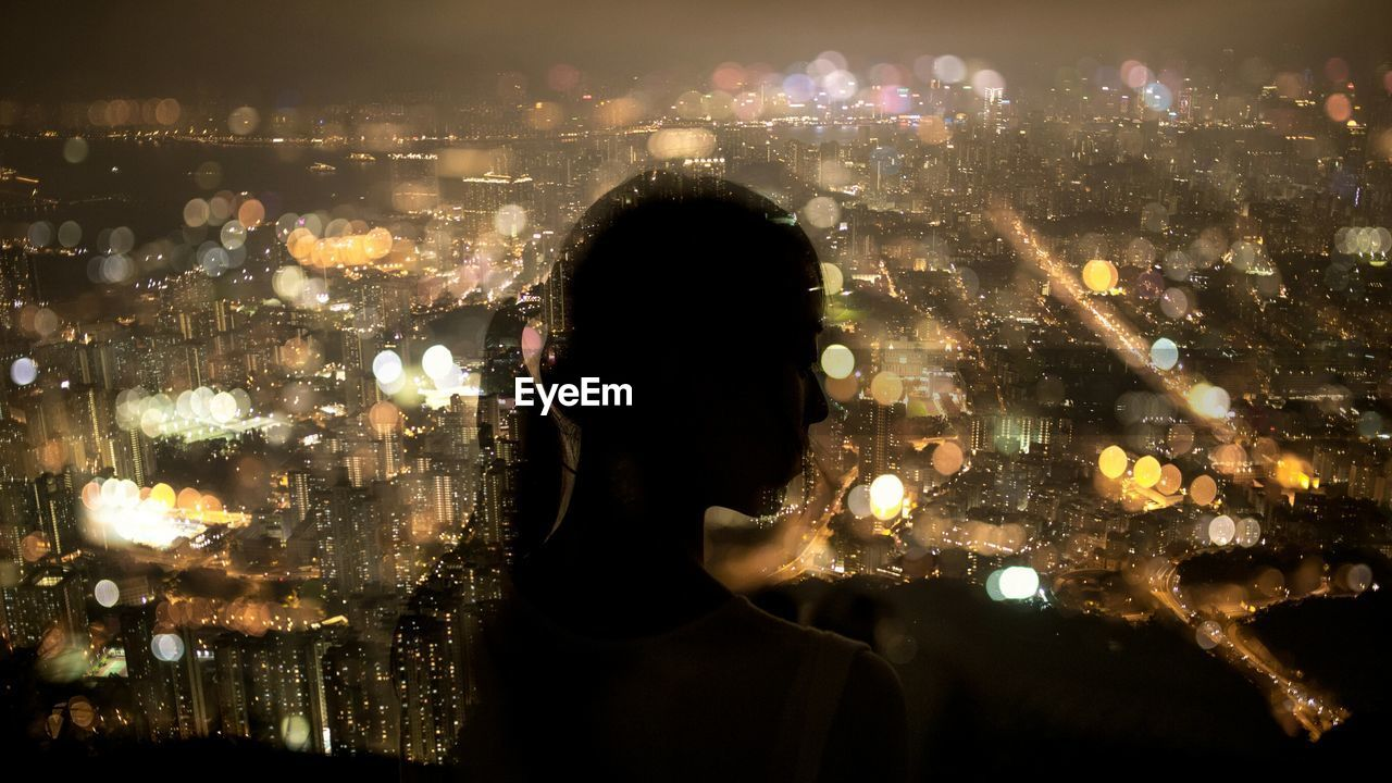 Silhouette Woman Looking At Illuminated Cityscape At Night