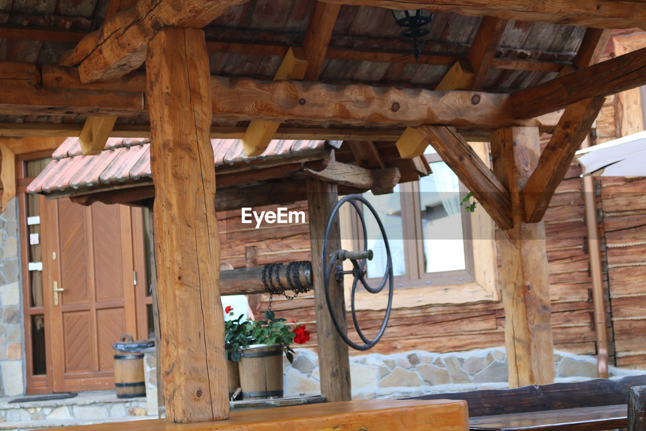 wood - material, architecture, built structure, no people, indoors, day, house, building, hut, log cabin, nature, old, roof, hanging, focus on foreground, ceiling, low angle view, roof beam, wheel