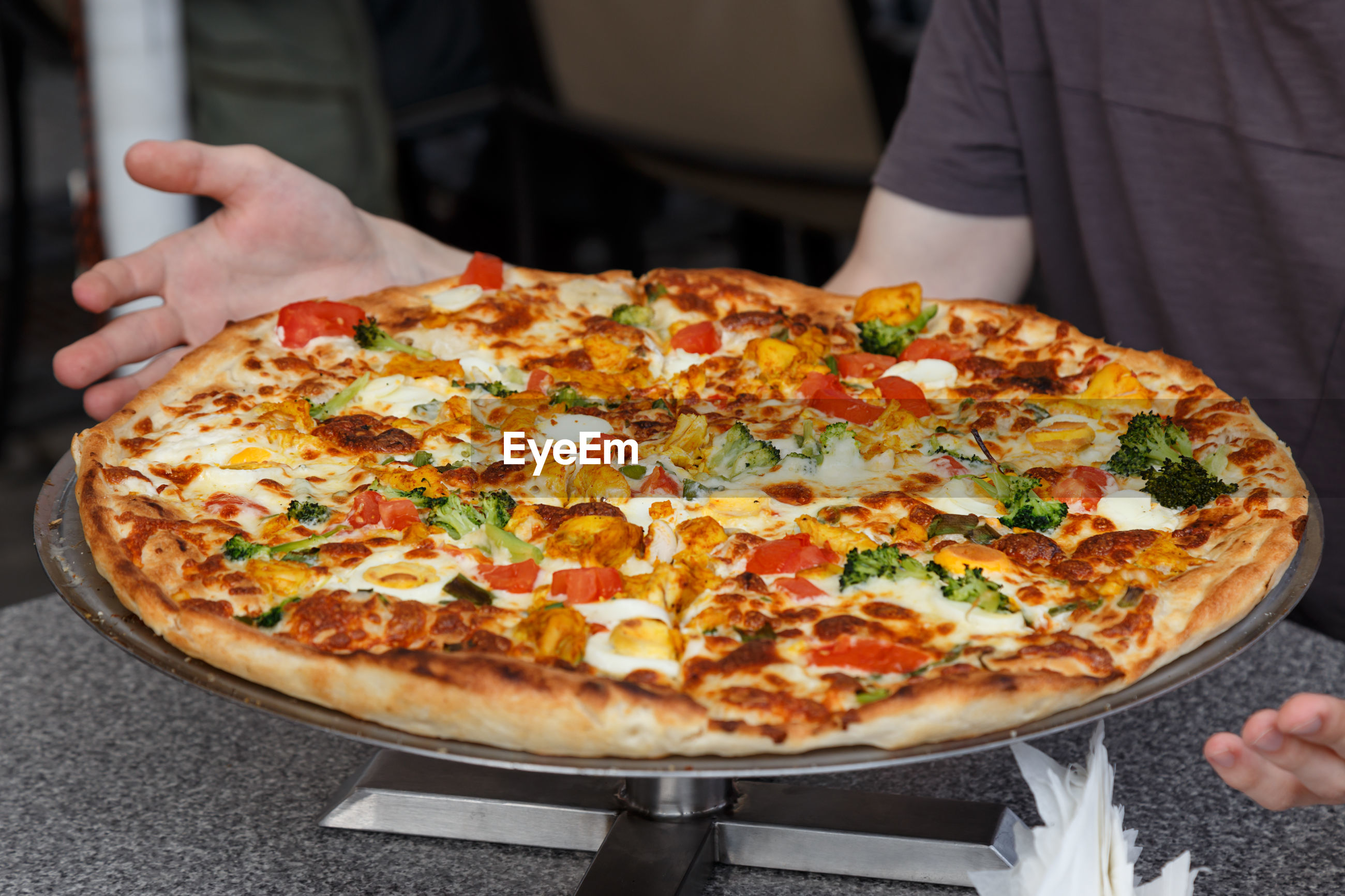 Midsection of man eating pizza