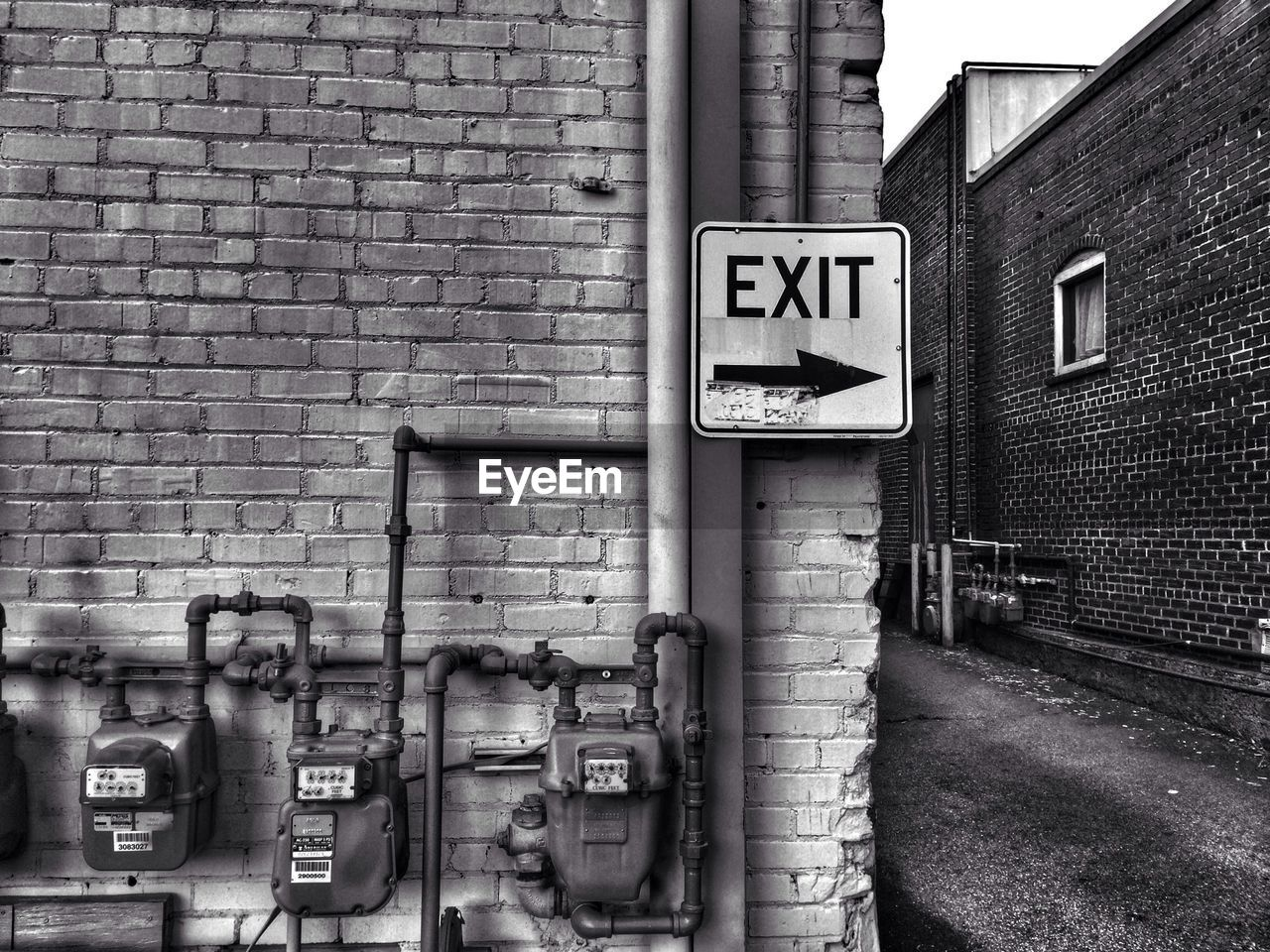 Close-up of exit sign on brick wall