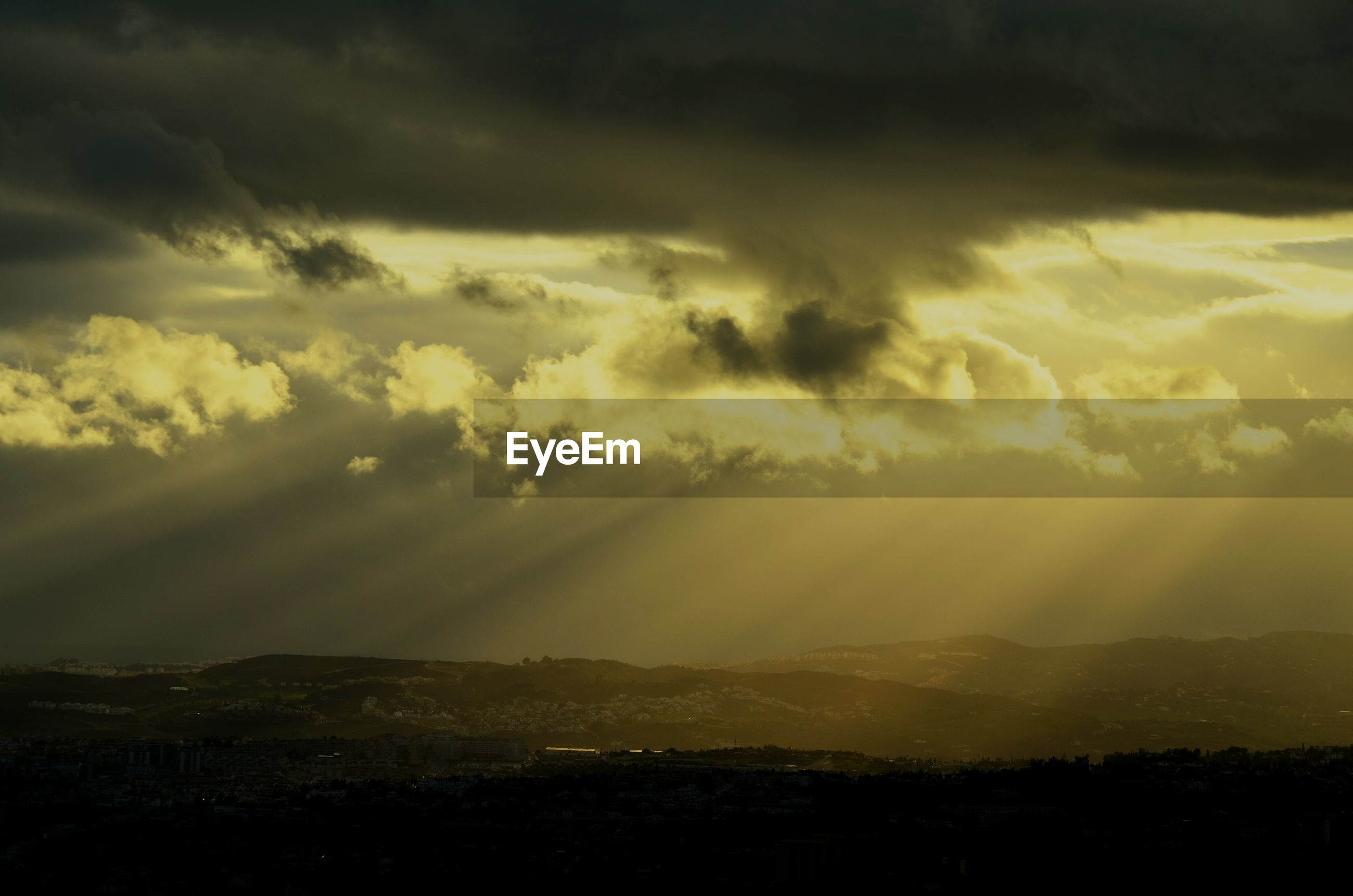 Sunbeams streaming from cloudy sky on landscape during sunset