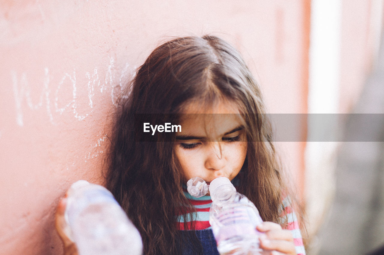 Girl Drinking Water While Leaning On Wall