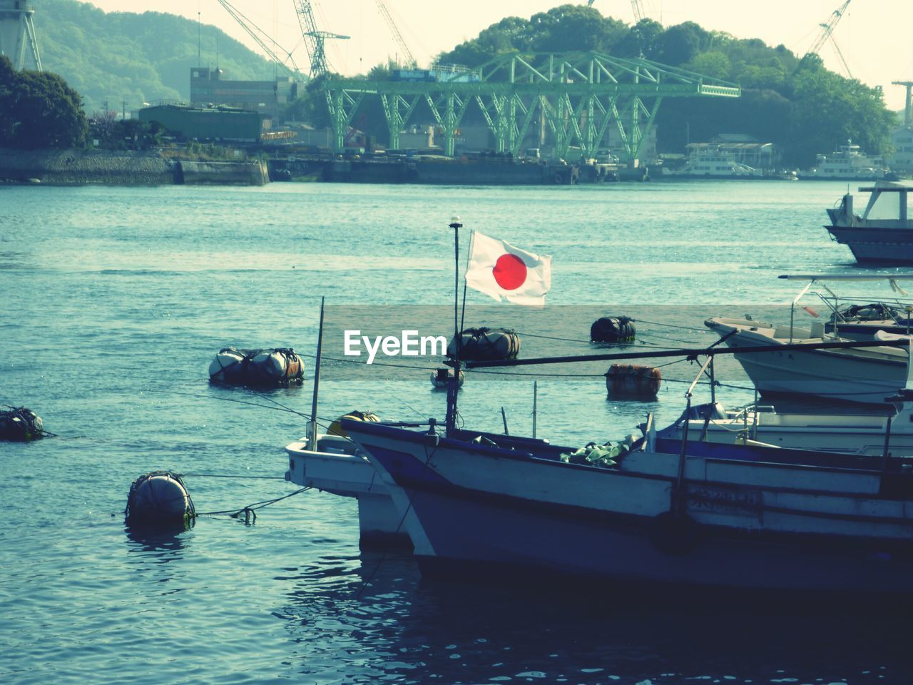 Boat With Japan Fag Moored In Sea Against Commercial Dock