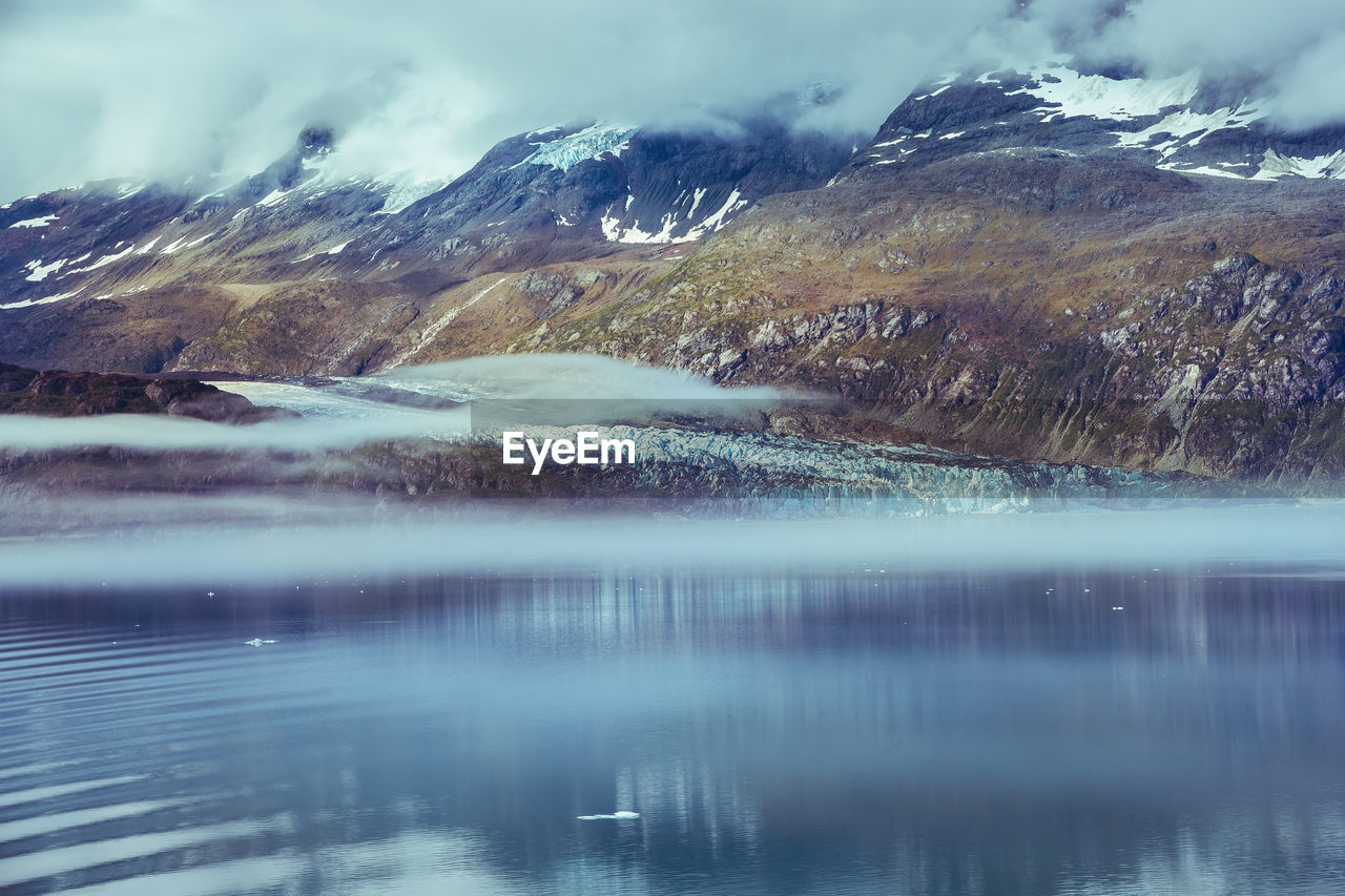 water, scenics - nature, beauty in nature, mountain, cold temperature, winter, tranquility, lake, tranquil scene, snow, nature, waterfront, sky, no people, environment, day, non-urban scene, reflection, outdoors, snowcapped mountain, ice, flowing water