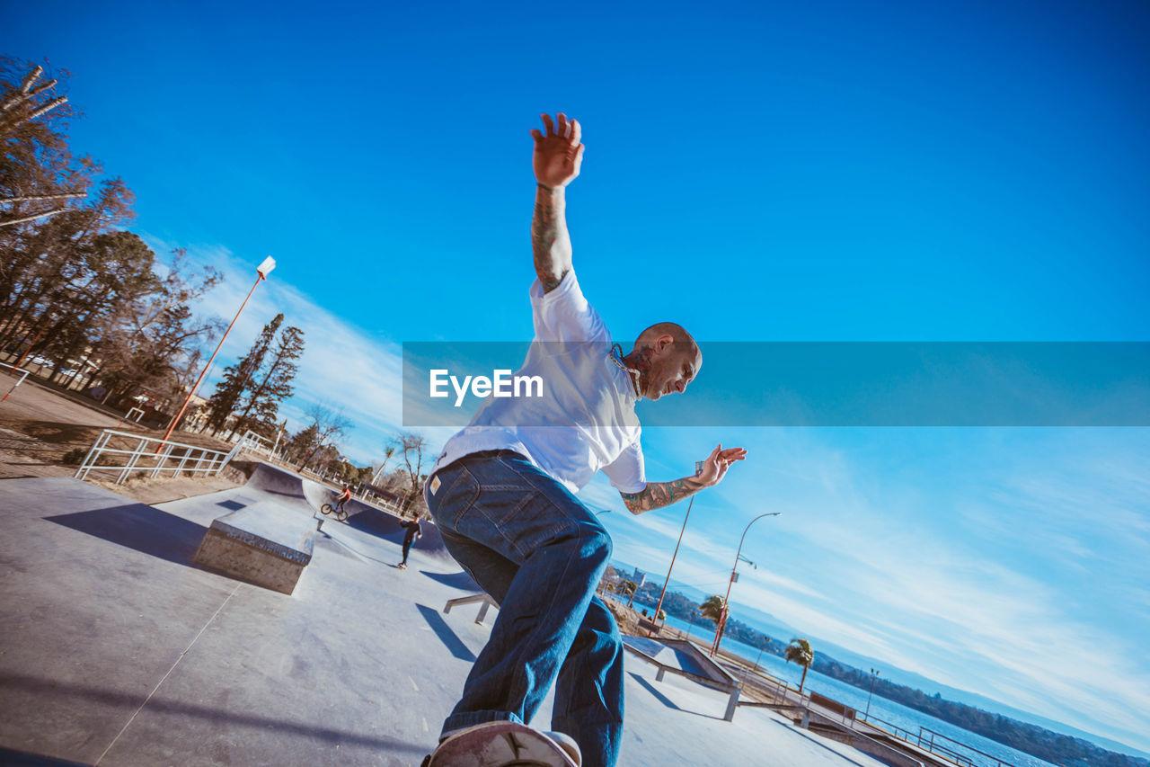 Man Skateboarding Against Blue Sky During Sunny Day