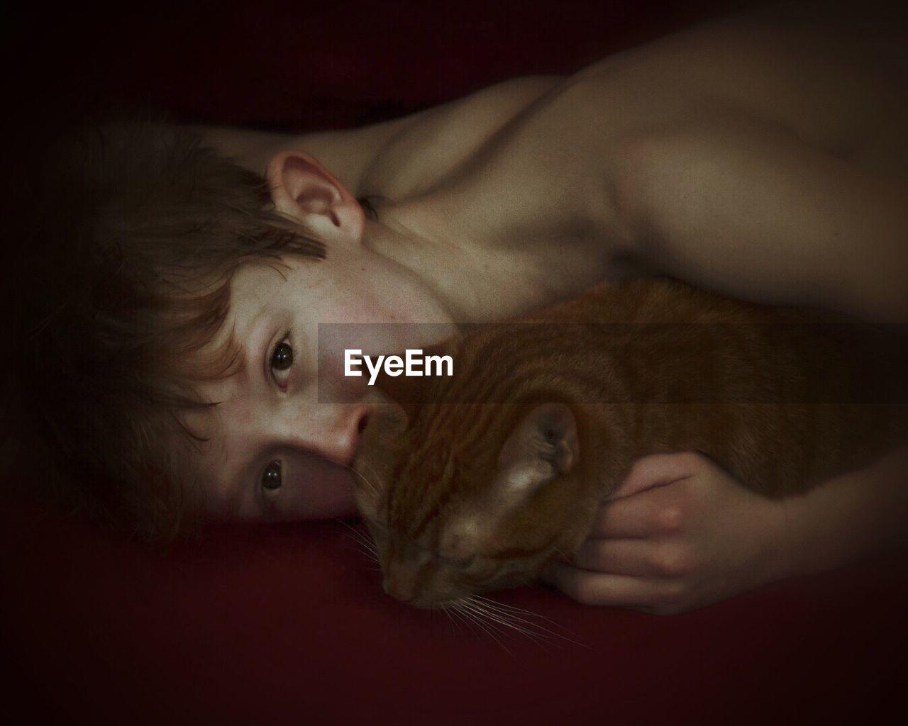 Portrait Of Shirtless Boy Embracing Cat