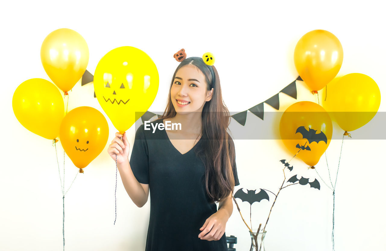 Young Woman With Balloons At Home During Halloween