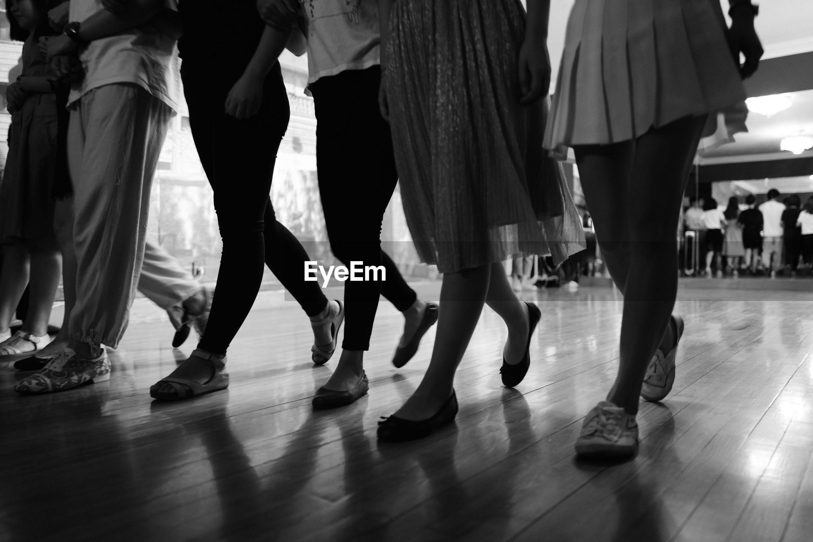 Low section of people dancing on hardwood floor