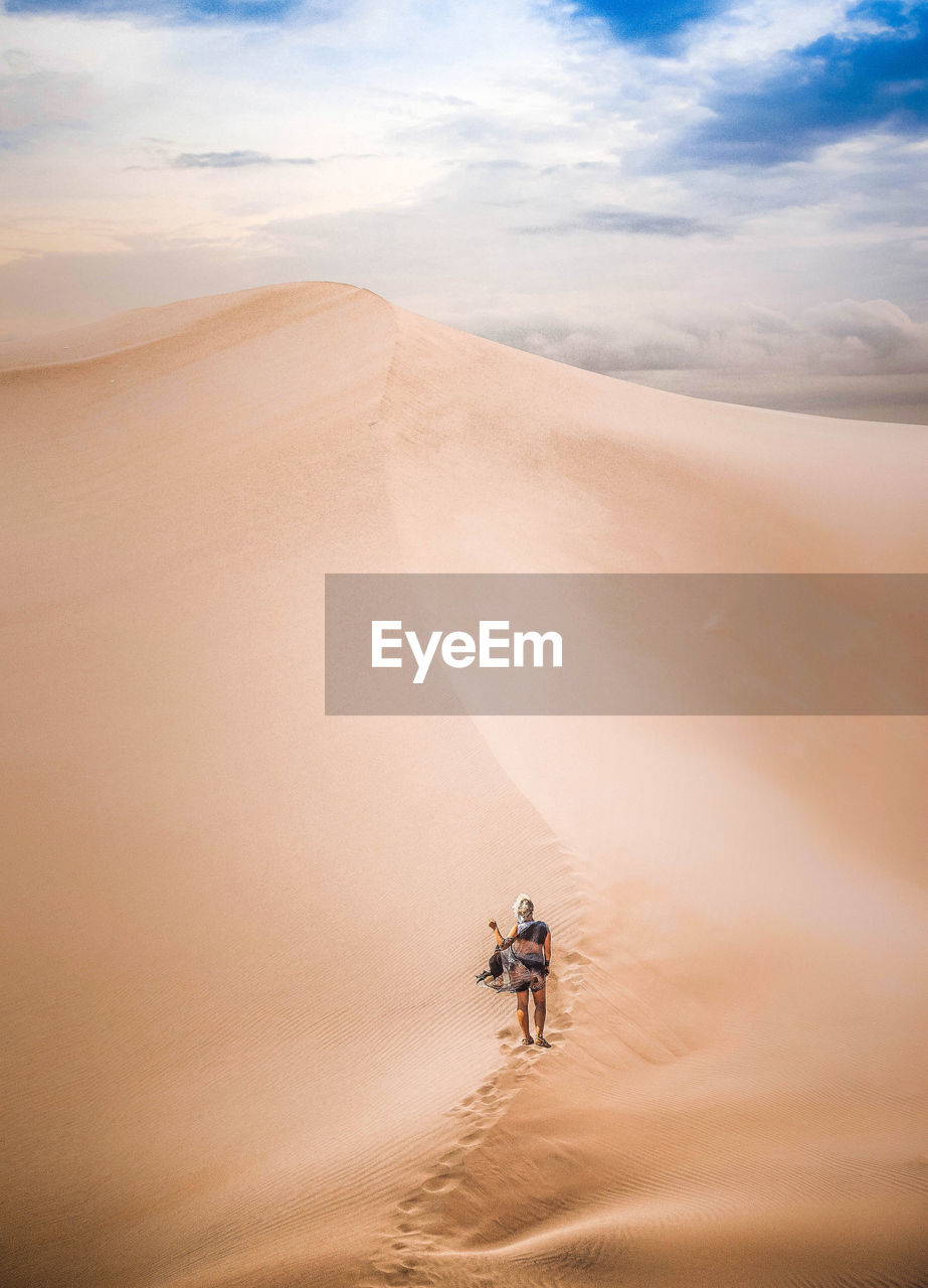 Rear view of woman standing on sand dune at desert