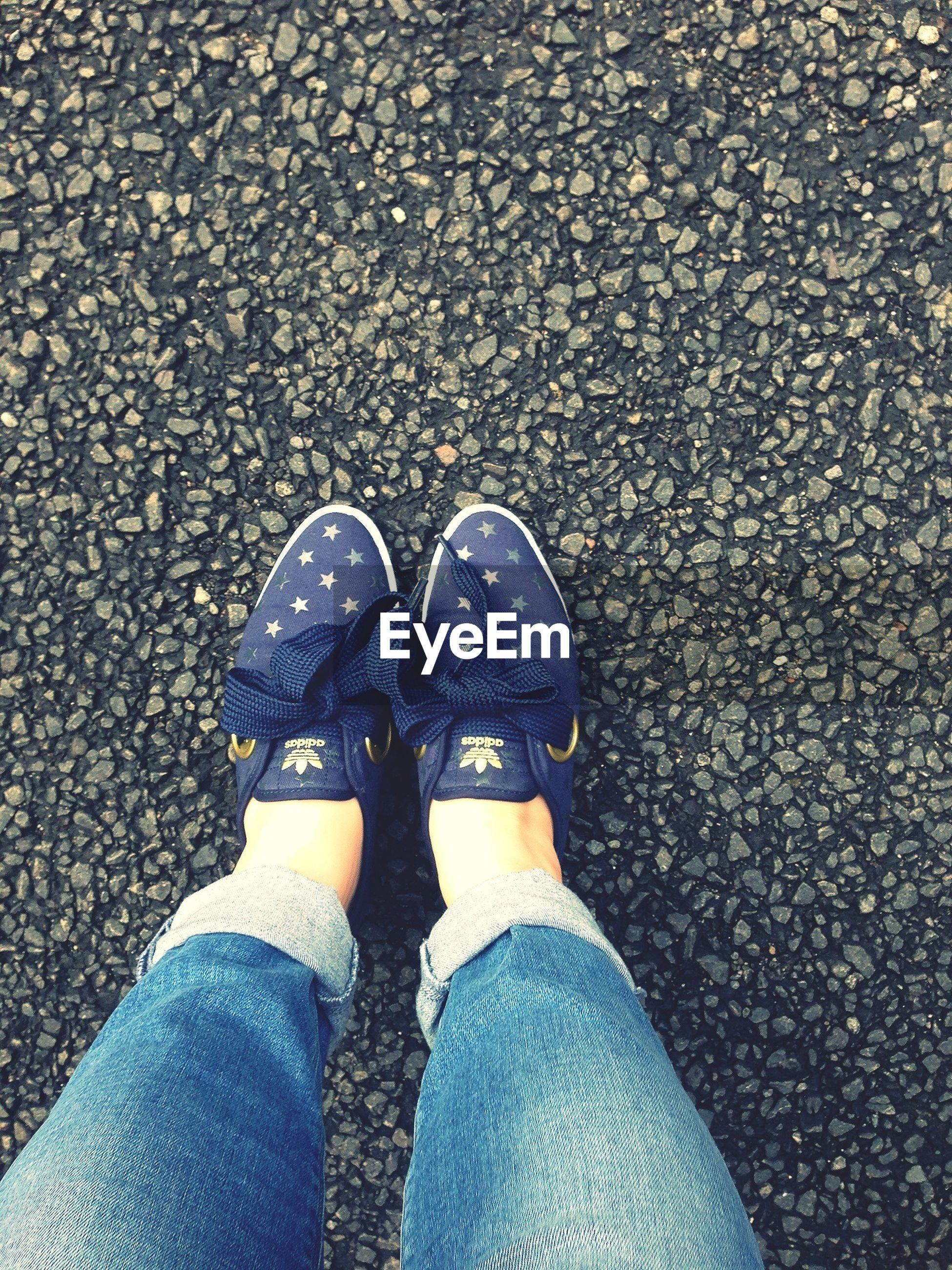 low section, person, shoe, personal perspective, standing, jeans, footwear, human foot, high angle view, lifestyles, men, street, leisure activity, directly above, canvas shoe, unrecognizable person, road
