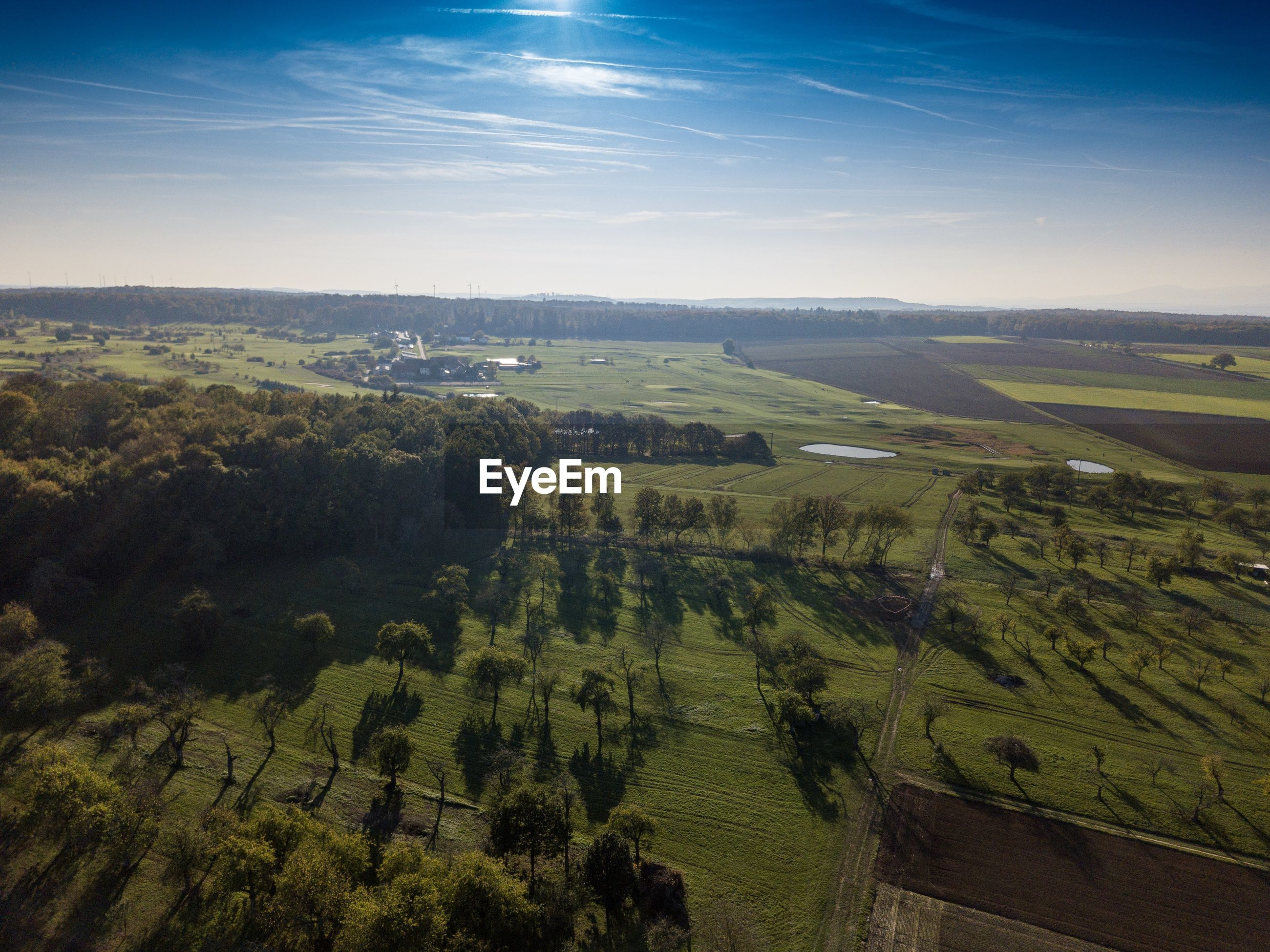 Scenic aerial shot agricultural field against sky