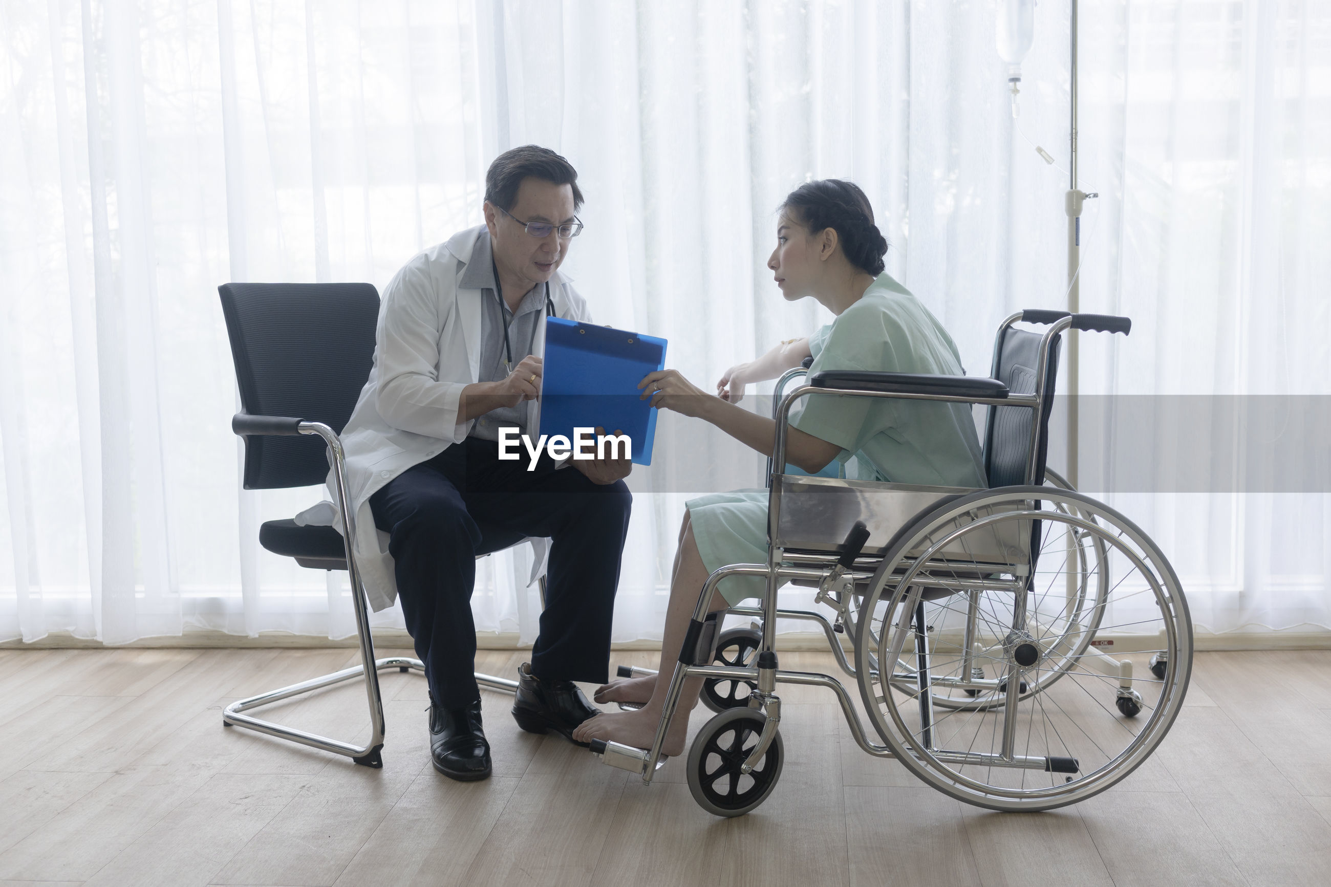 Doctor talking with patient while sitting at hospital