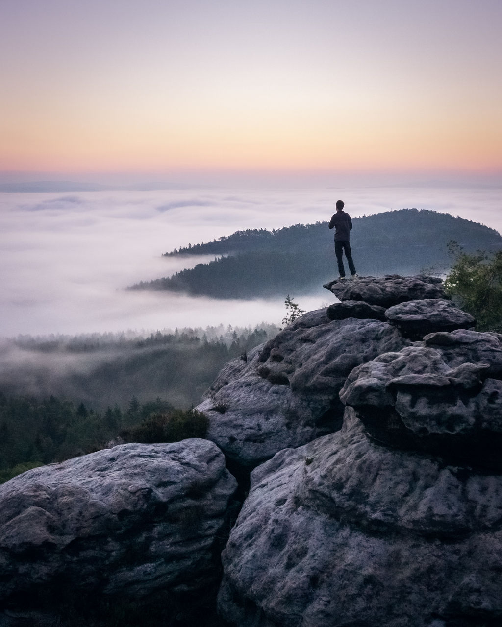Man standing on rock against sky during sunrise above the clouds