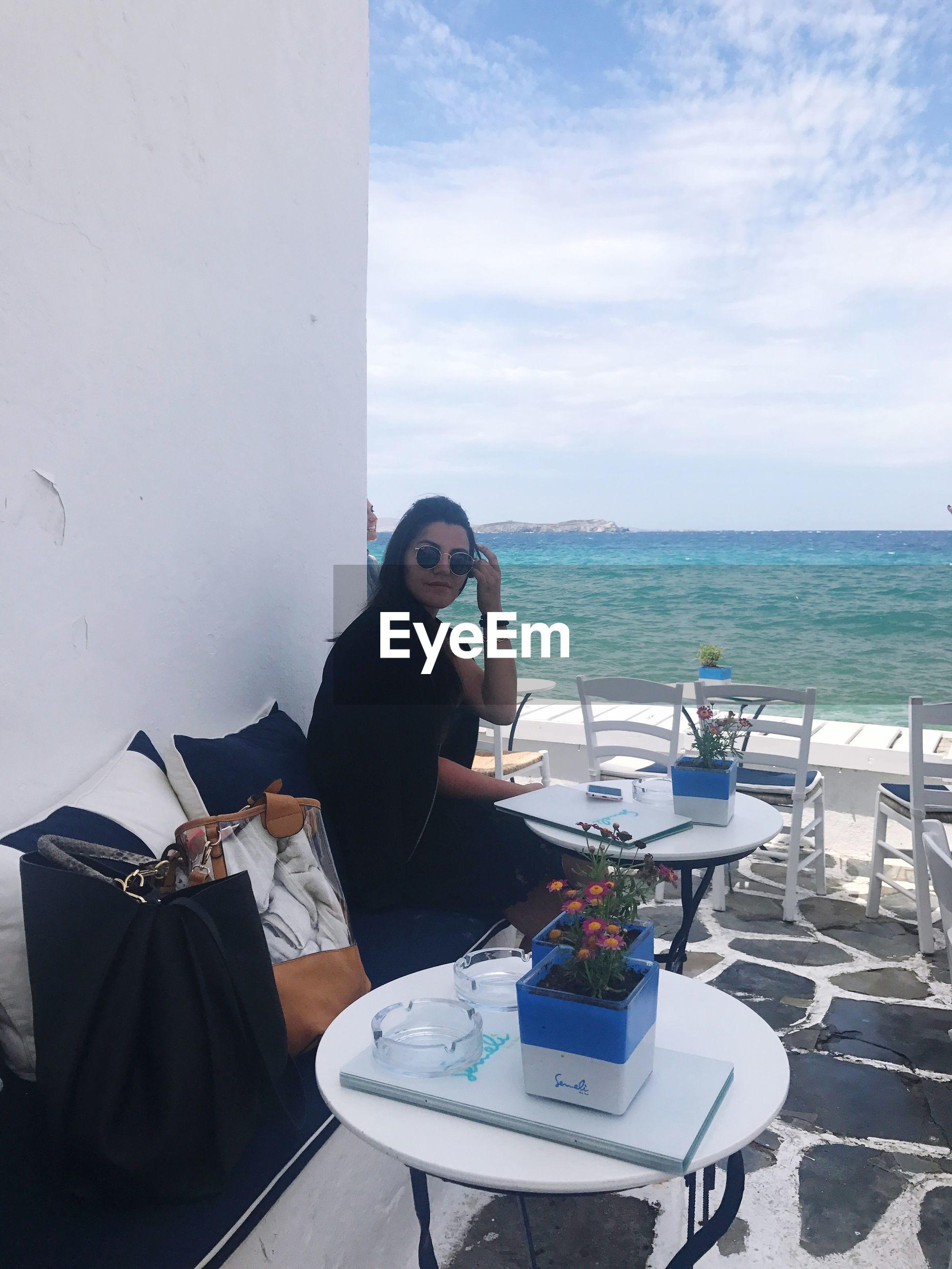 sea, wireless technology, one person, real people, technology, mobile phone, sky, sitting, using phone, horizon over water, table, portable information device, communication, food and drink, women, day, young adult, young women, water, outdoors, nature, photography themes, people