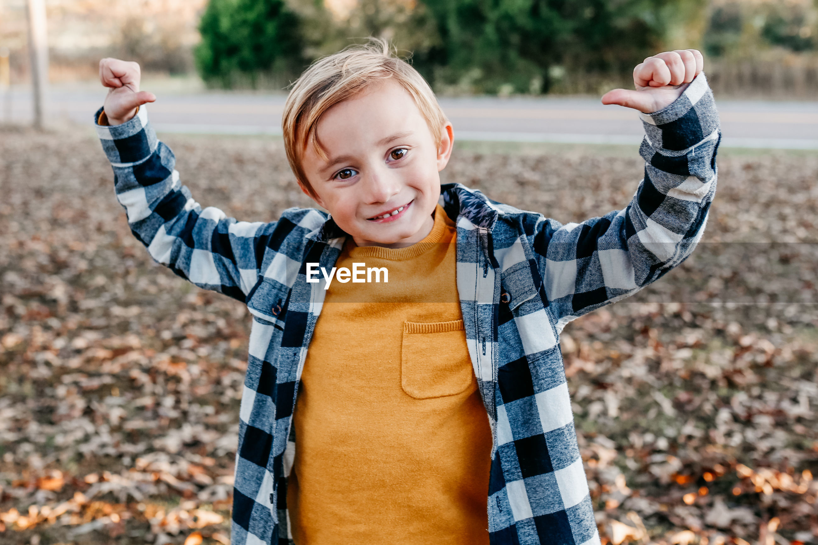 Portrait of smiling boy gesturing while standing on land