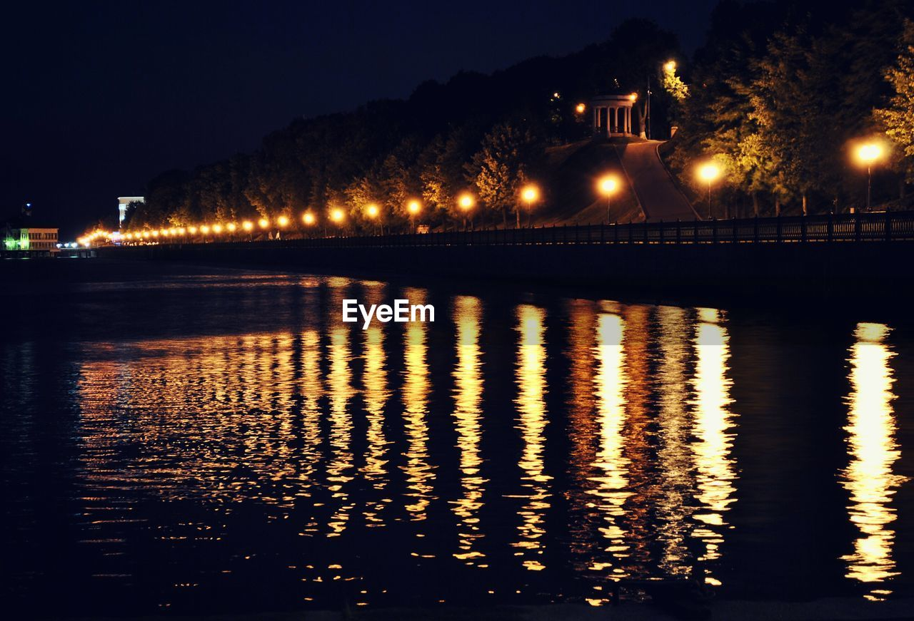 illuminated, night, reflection, water, architecture, waterfront, built structure, building exterior, no people, outdoors, river, sky, nature, beauty in nature, chain bridge