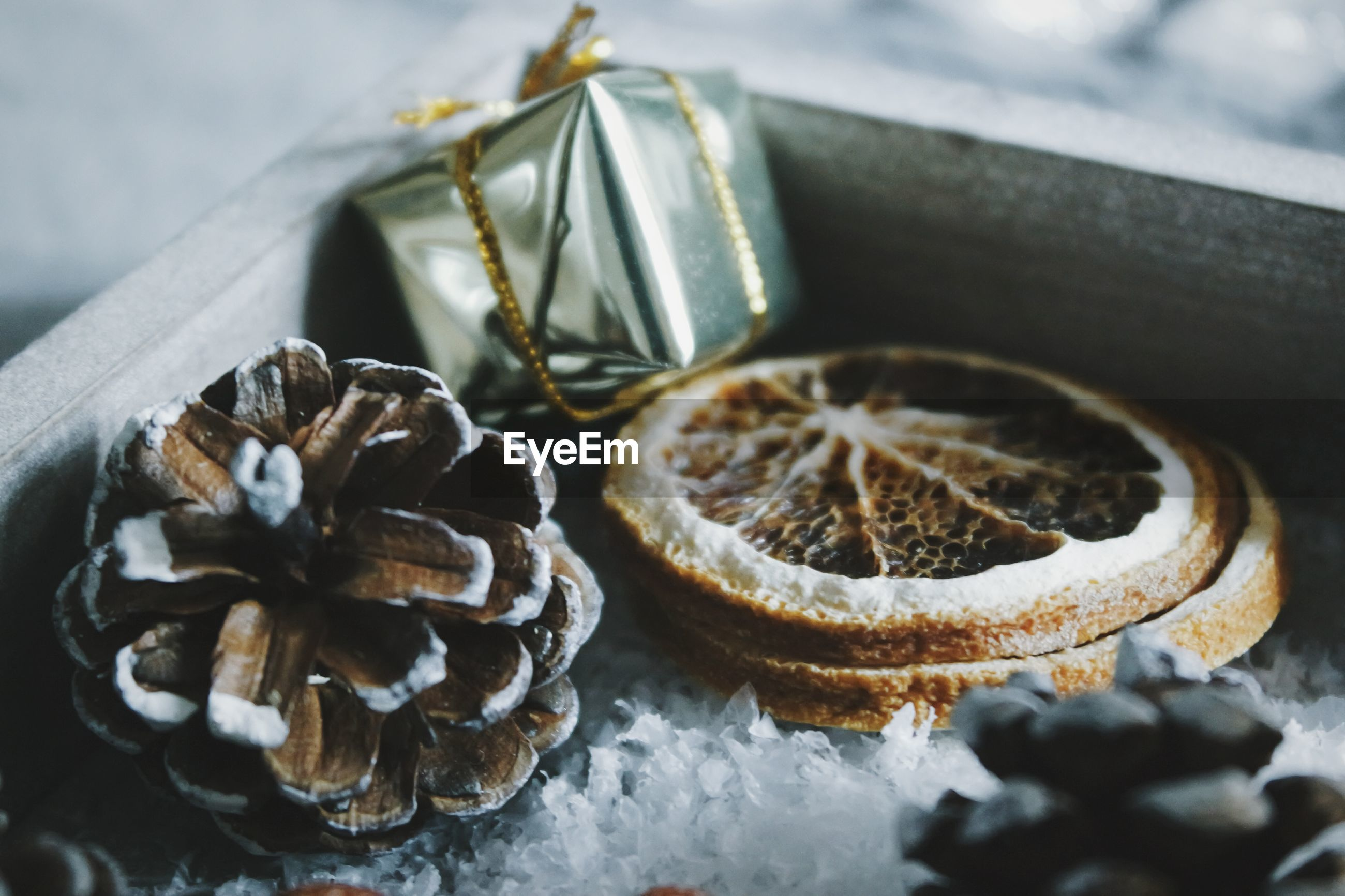 Close-up of pine cones with dry orange slices with christmas present in box