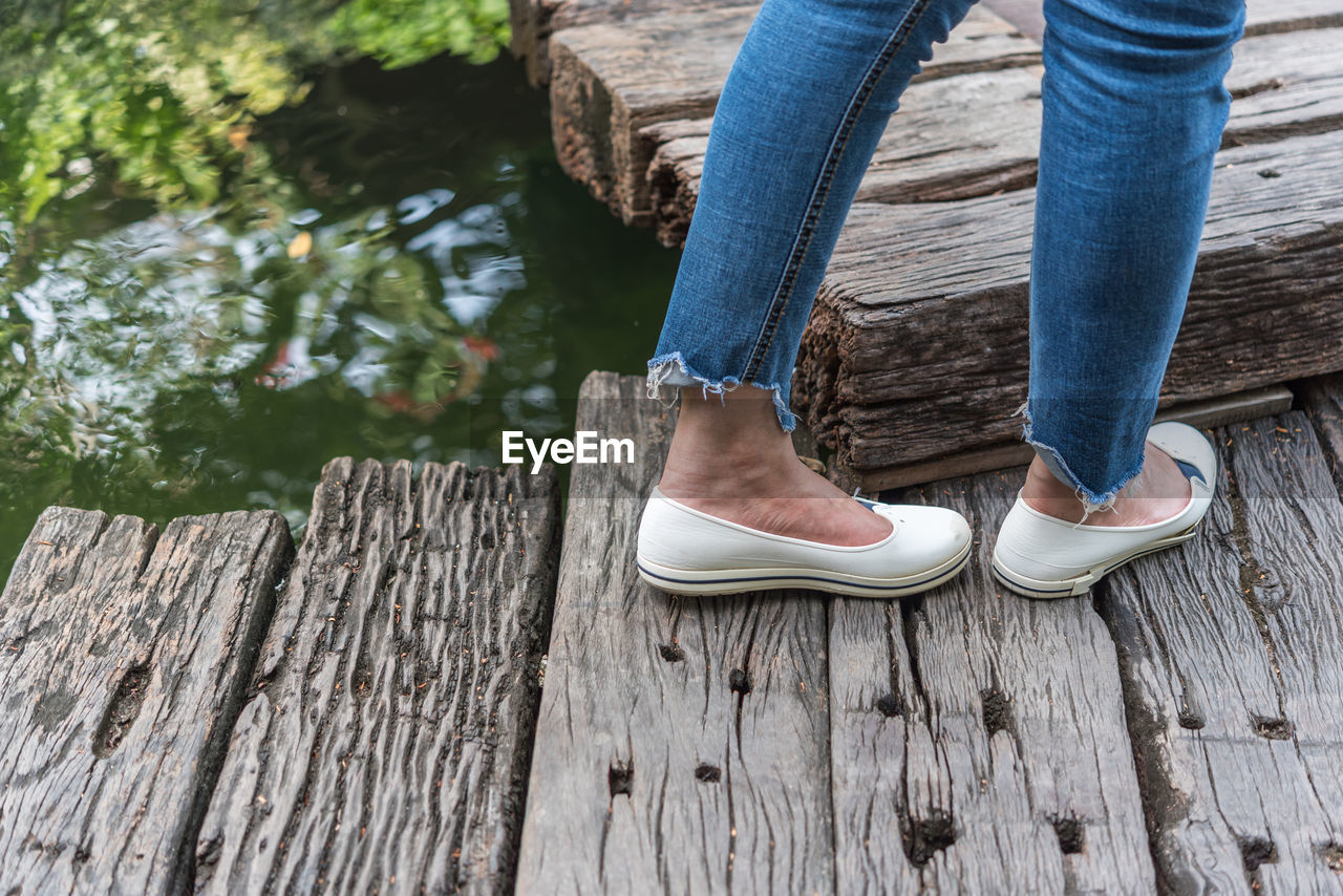 low section, wood - material, human leg, shoe, standing, day, jeans, real people, one person, casual clothing, outdoors, women, human body part, nature, close-up, people