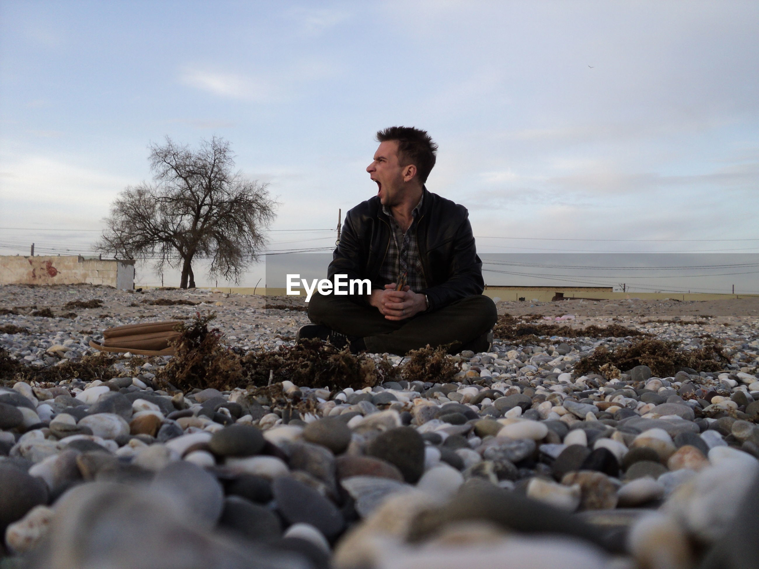 Mid adult man yawning while sitting on pebbles against sky