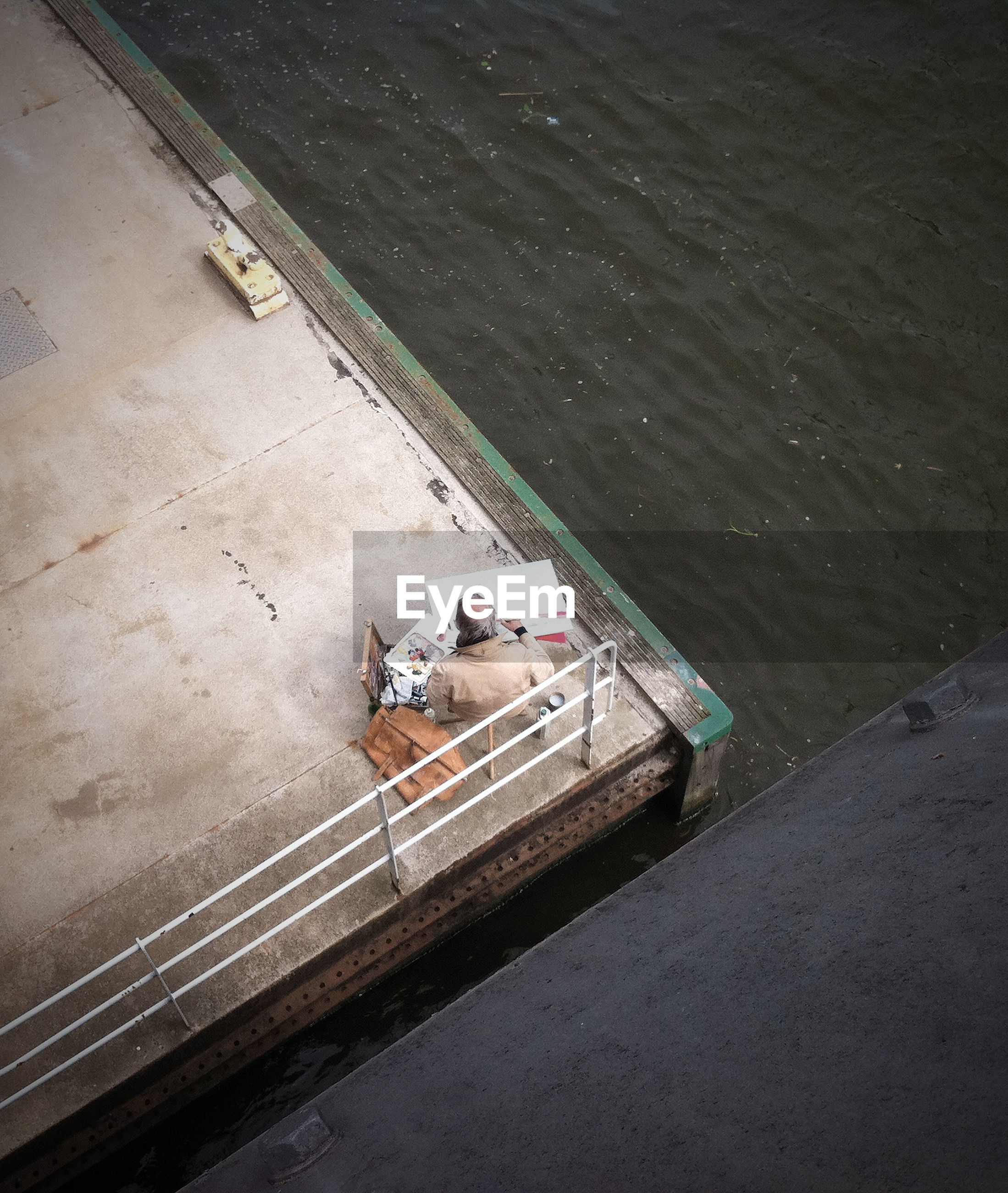 High angle view of painter sitting on pier by sea