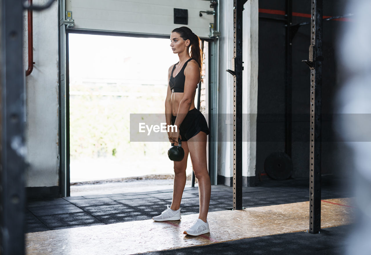 Woman Lifting Weight While Standing In Gym