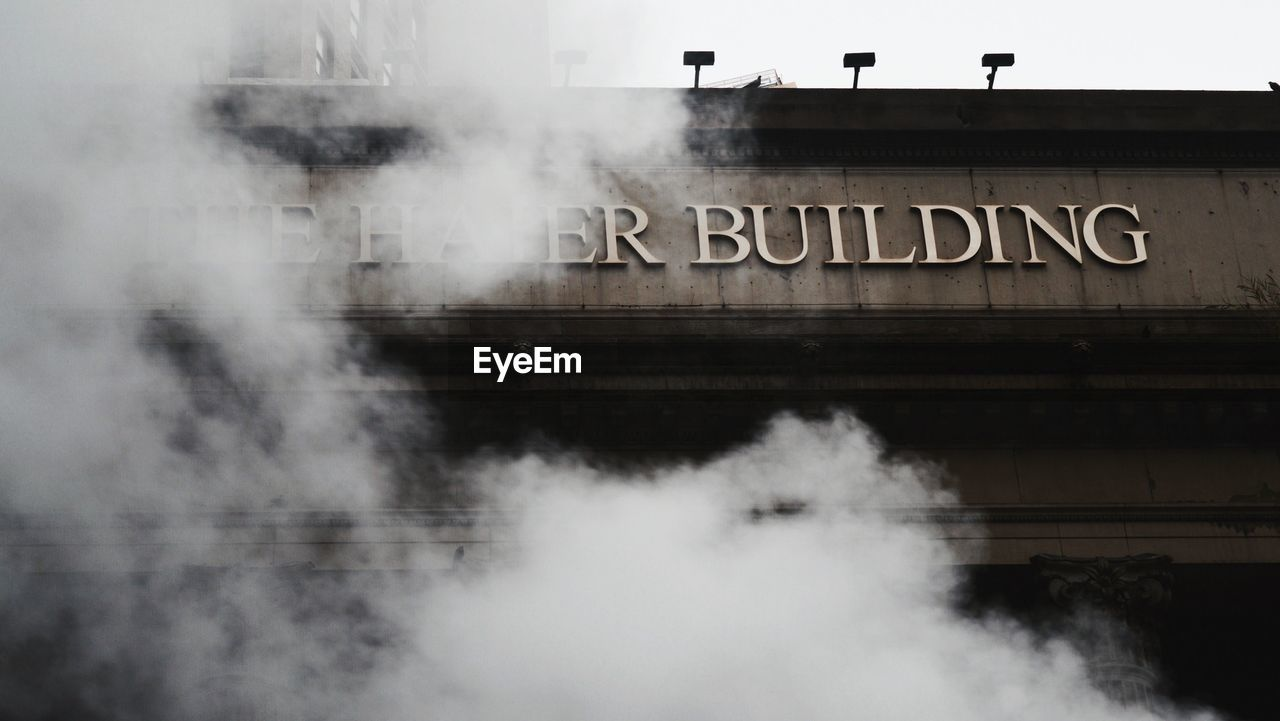 smoke - physical structure, text, architecture, built structure, building exterior, communication, transportation, day, outdoors, steam, no people, water, steam train